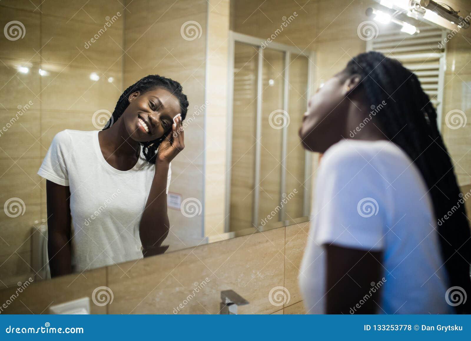 Ren framsida för härlig ung afrikansk kvinna från skönhetsmedel och att le, medan stå mot en spegel i badrum
