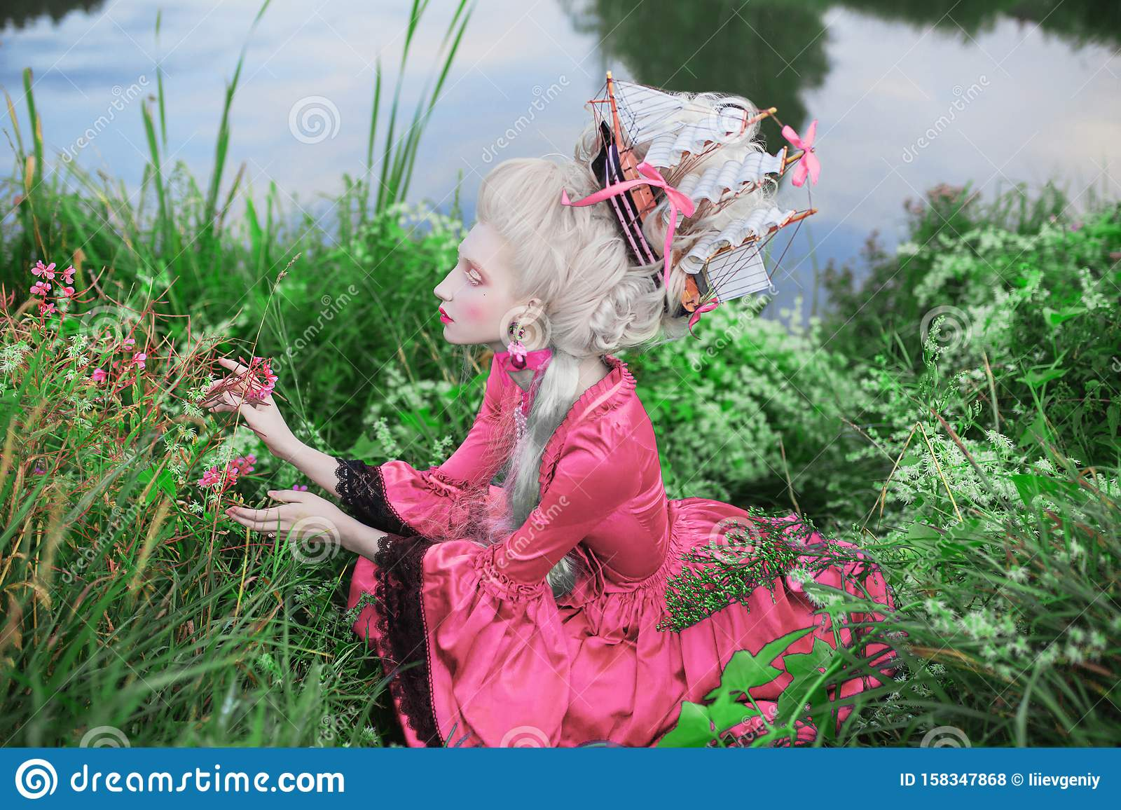 Renaissance princess with blonde hair. Fairytale rococo queen with ship in hairstyle on nature background. Rococo queen in pink