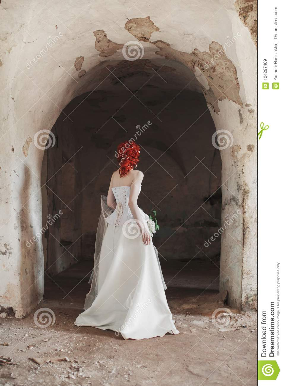 Renaissance redhead mysterious princess with hairstyle in old castle. Doll in corset. Victorian princess in palace.