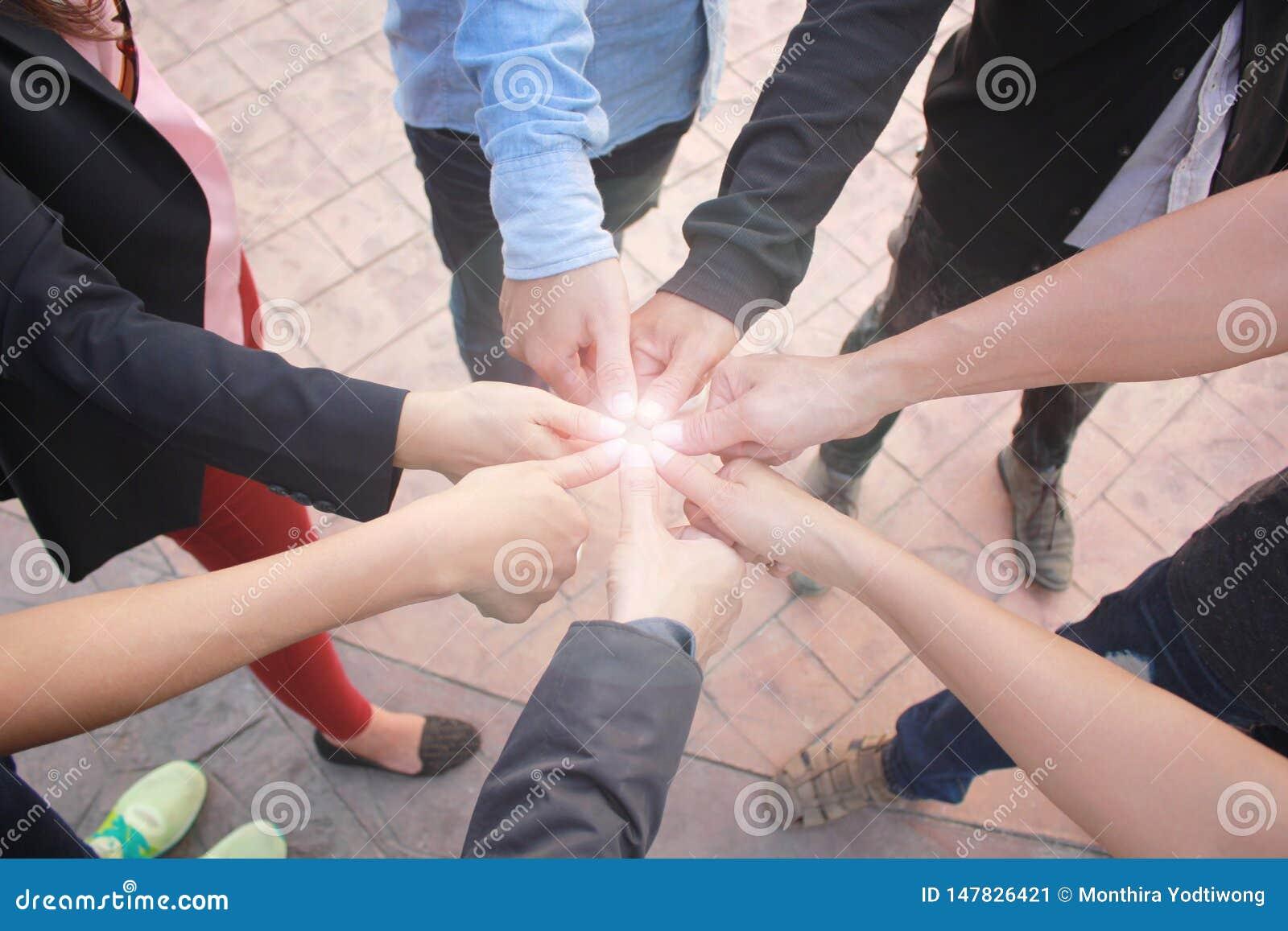 Rencontrant le concept de travail d équipe, le groupe d amitié avec des mains montrant l unité et les pouces sur le fond concret