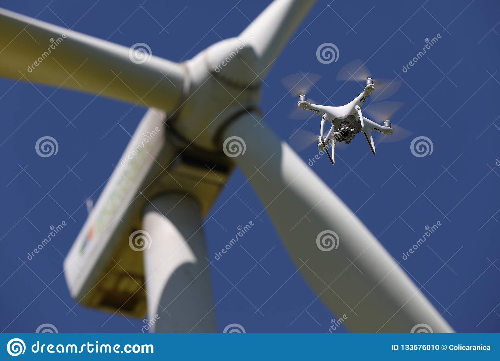 Drone hovering over wind turbines, renewable energy
