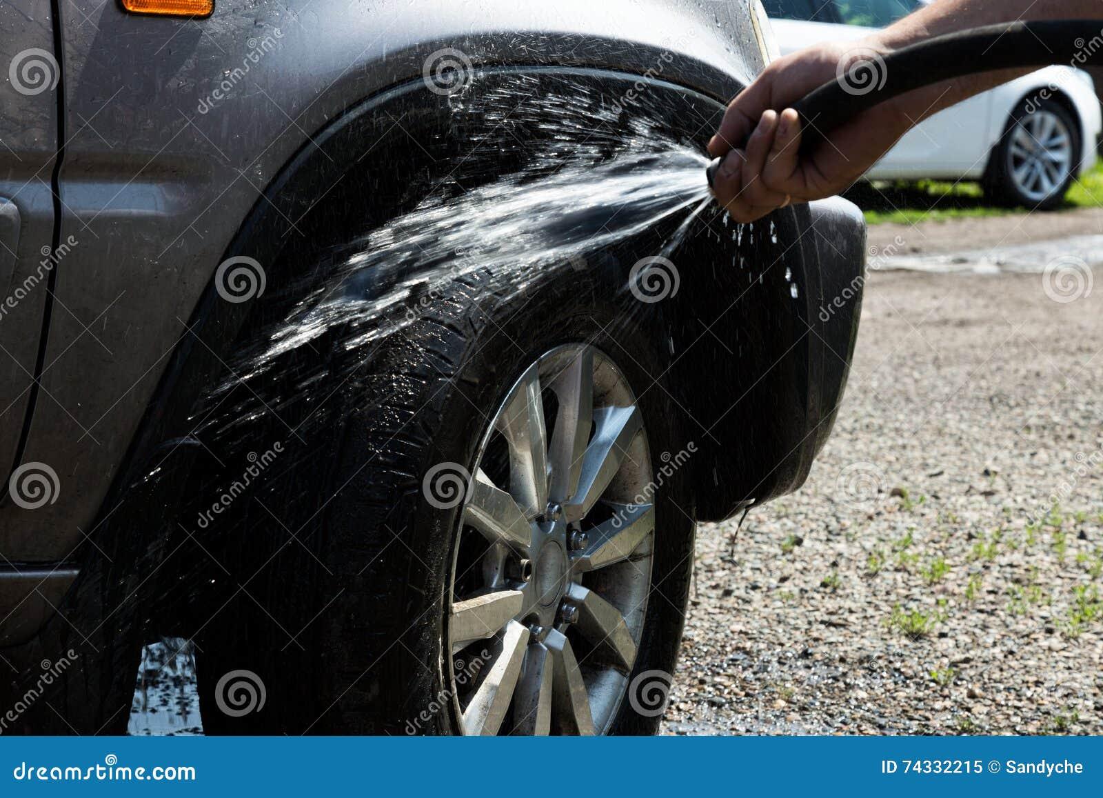 Rengöringwash för ung man försiktigt hans favorit- bilhjul