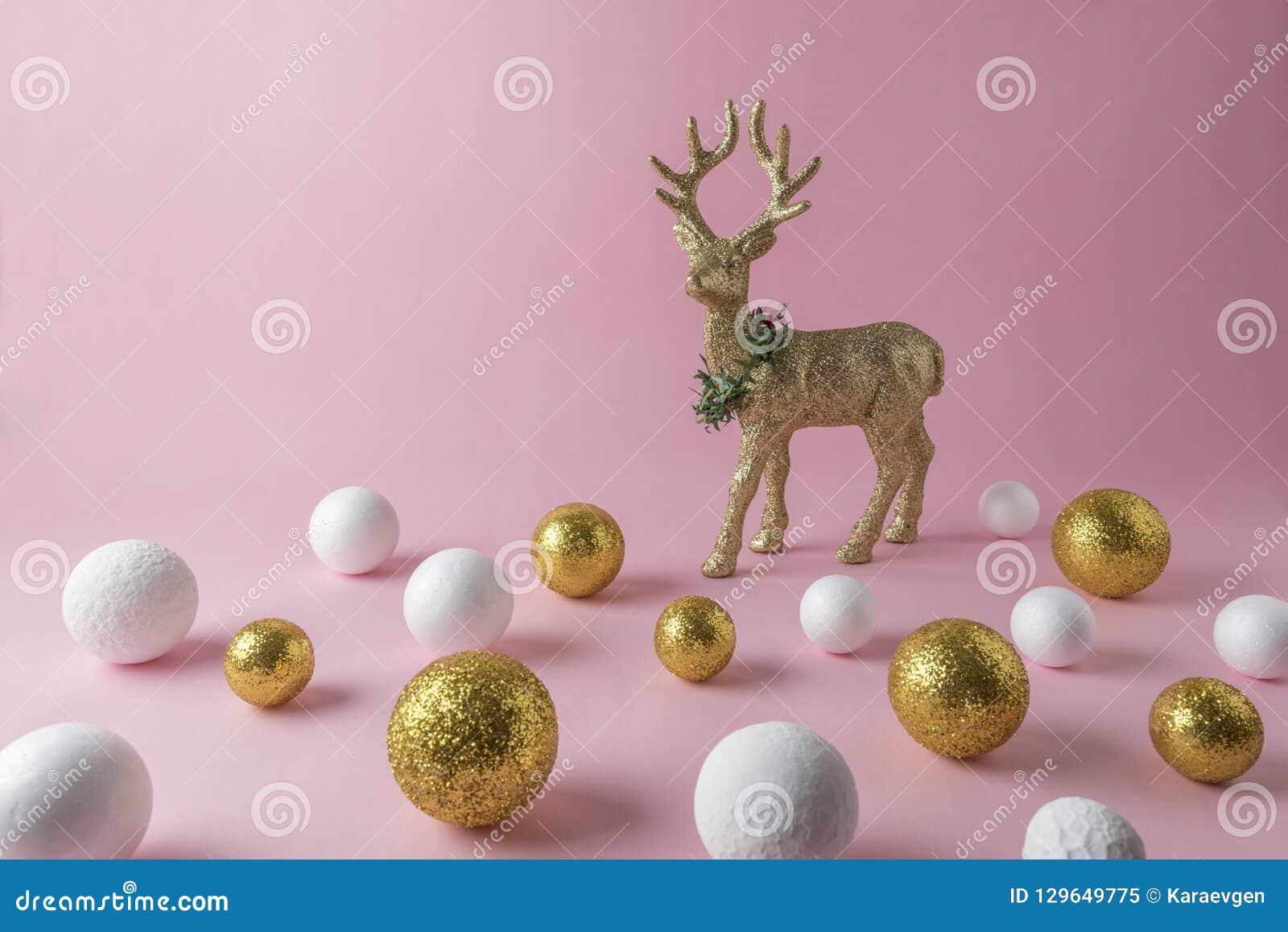 Renne de scintillement d or avec de l or et décoration blanche de boule de scintillement sur le fond rose