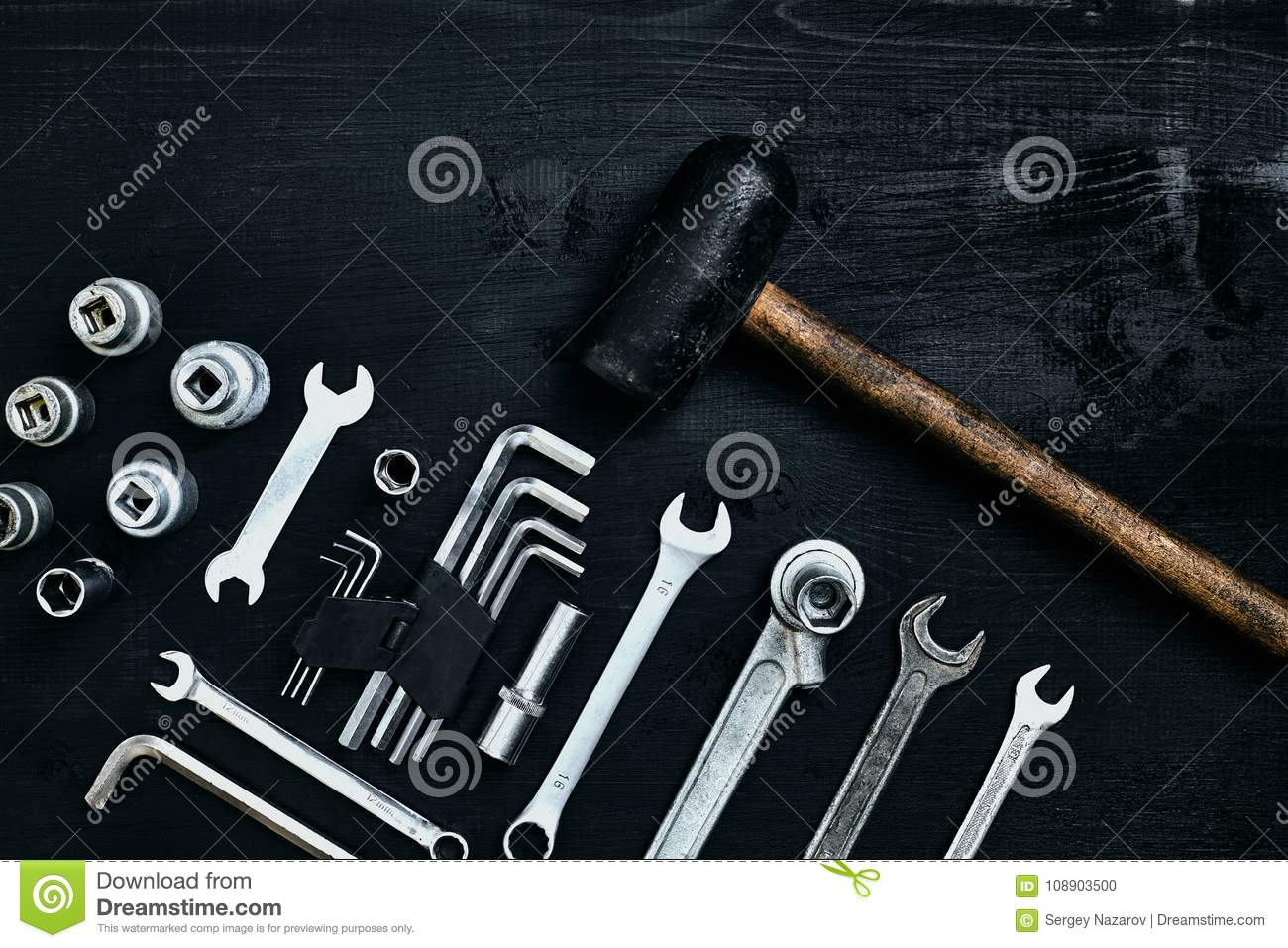 Renovating a car. A set of repair tools- hex keys, a hammer and a screwdriver on a black wooden background. Close up