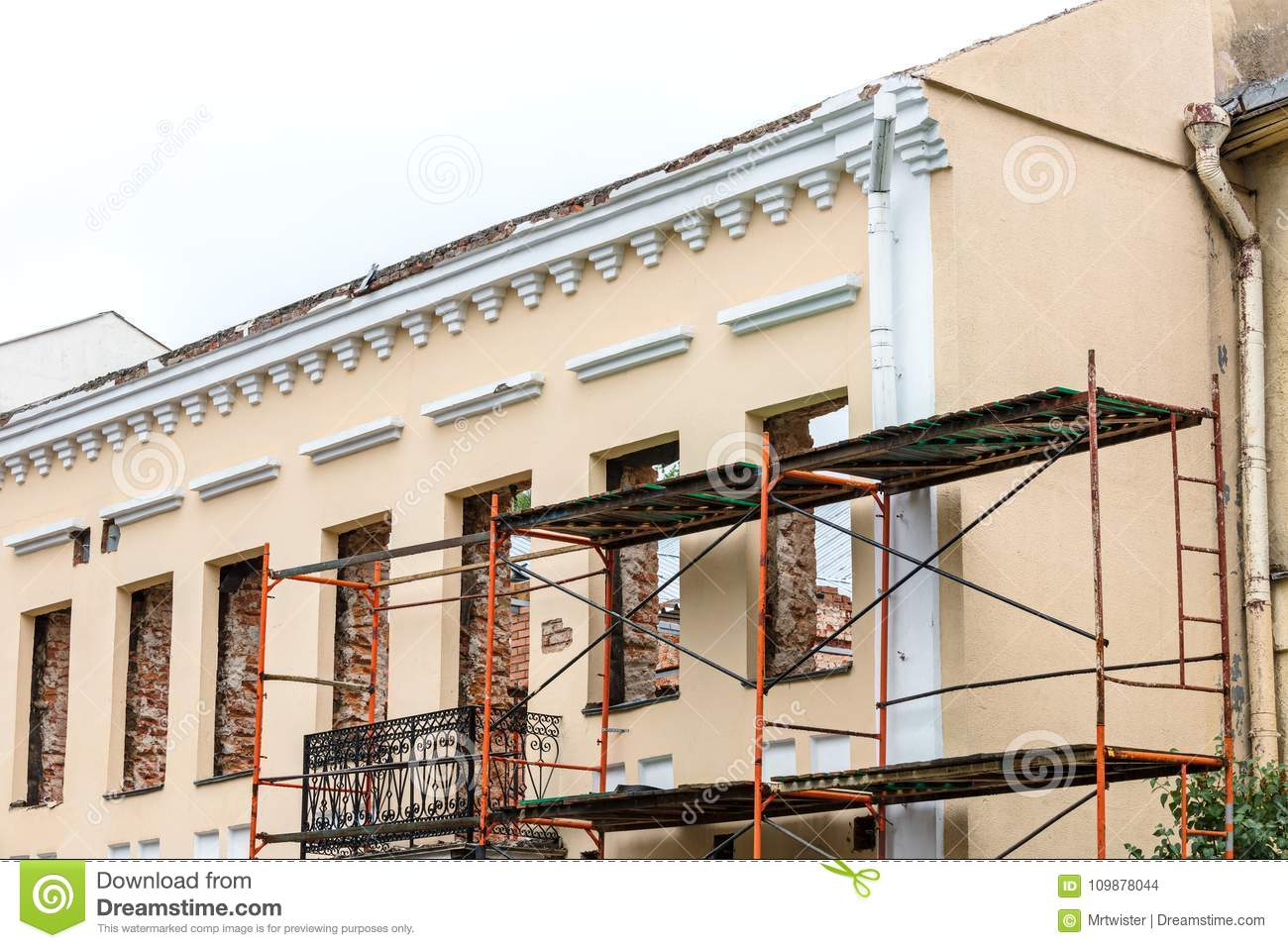 renovation of old residential building with scaffolding near facade wall