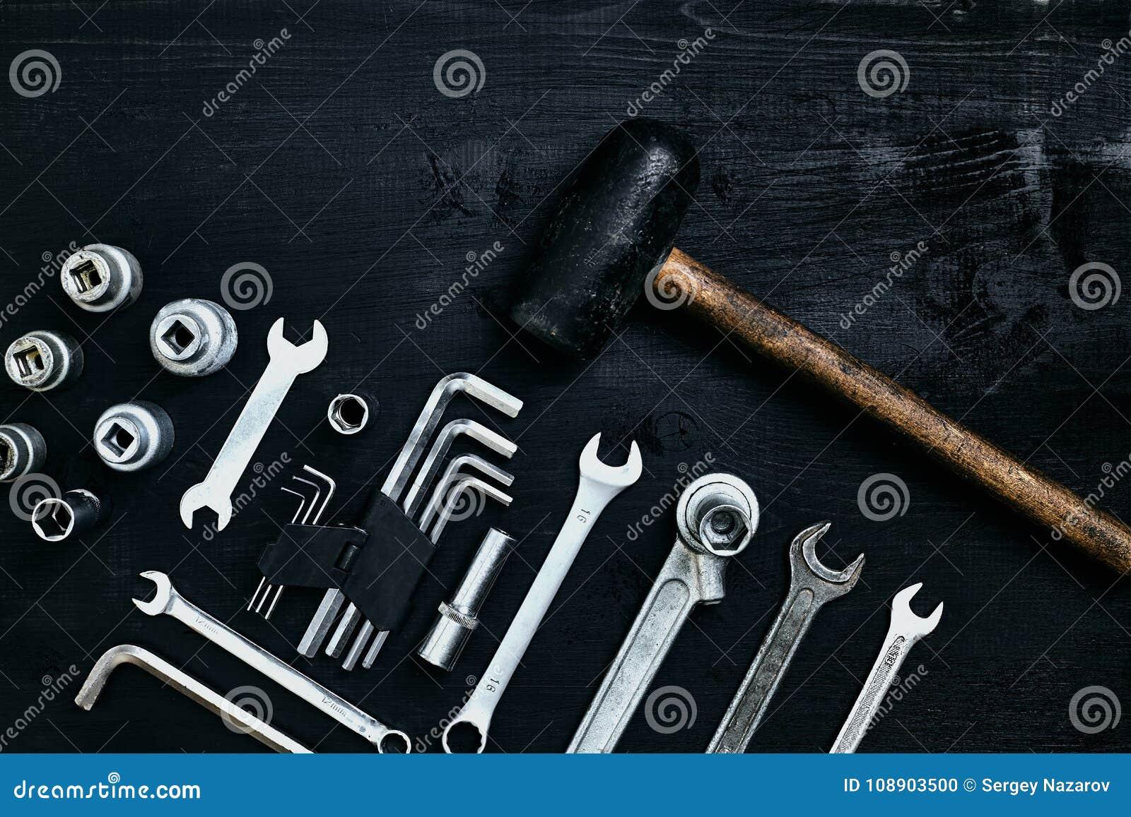 Renovera en bil En uppsättning av reparationshjälpmedel förhäxer tangenter, en hammare och en skruvmejsel på en svart träbakgrund