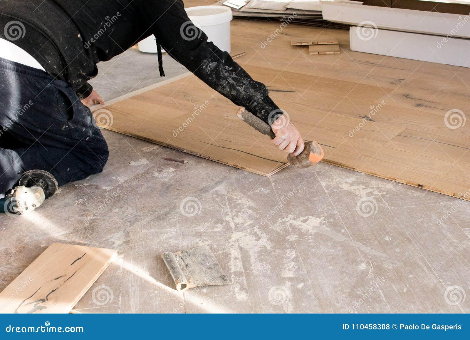Renovering av en lägenhet, den kompetenta arbetaren använder en plast- hammare