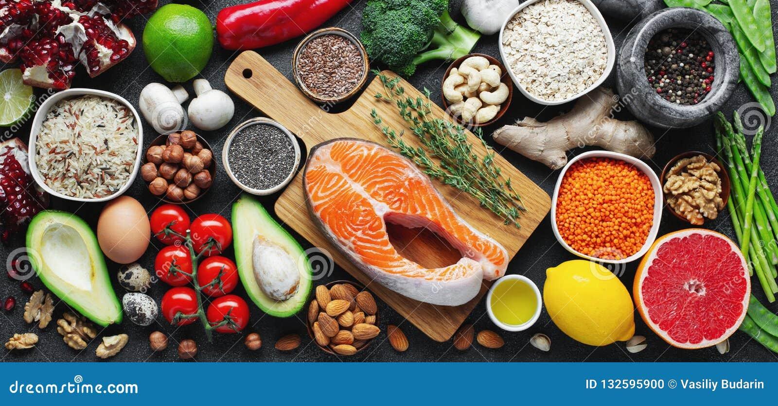 Rent ätaval för sund mat: fisk frukt, muttrar, grönsak, frö, superfood, sädesslag, bladgrönsak på svart betong