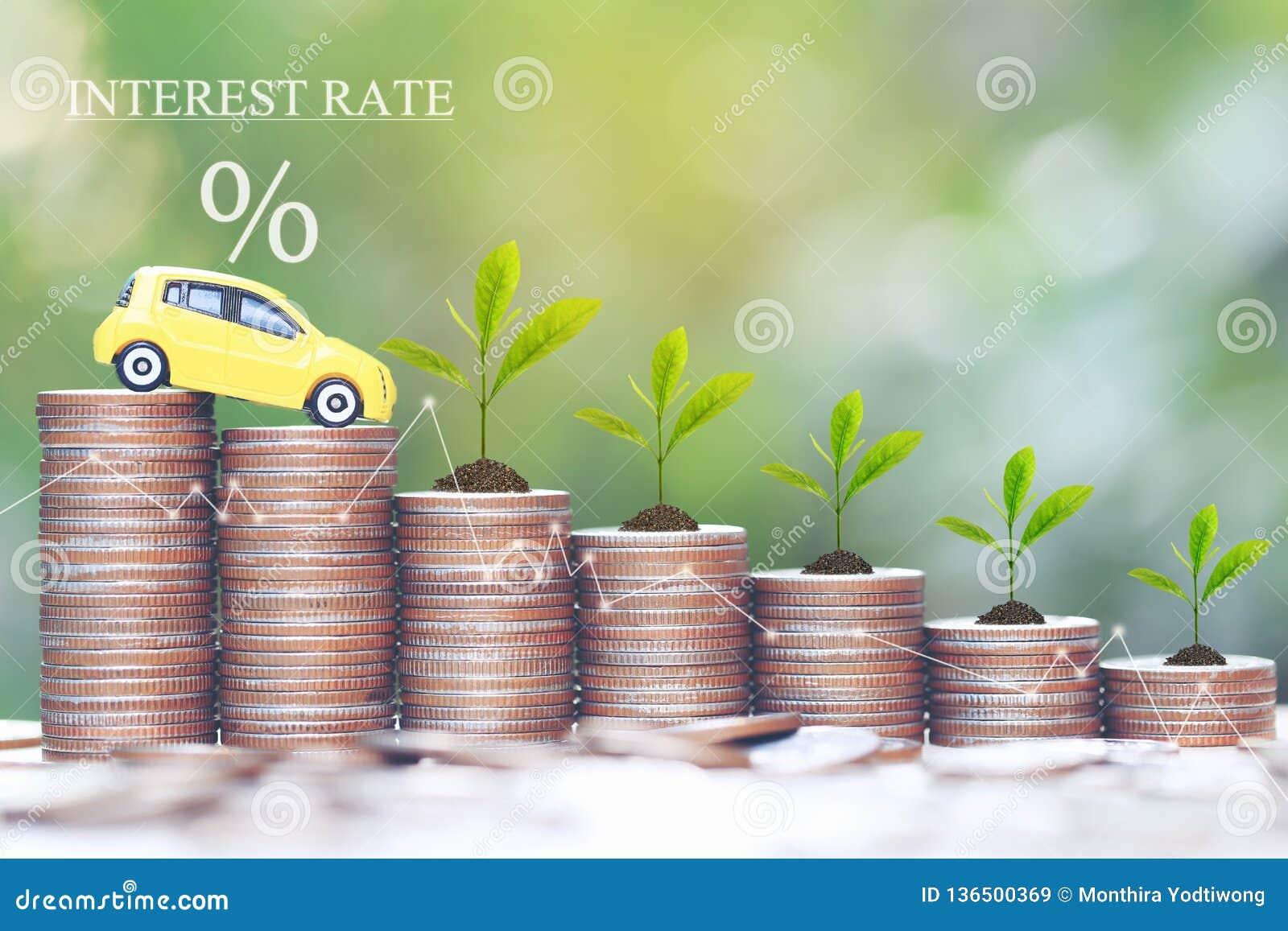Rentevoet en Bankwezenconcept, het Miniatuur gele automodel en Installatie groeien op stapel van muntstukkengeld op natuurlijke g