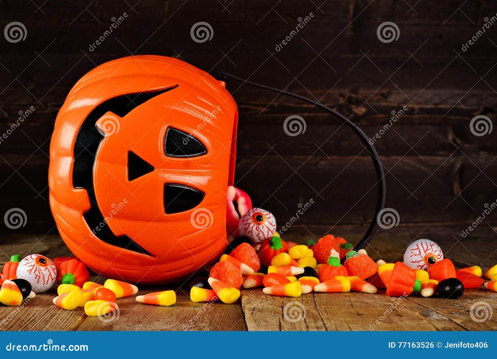 Renversement du seau de sucrerie de lanterne de Halloween Jack o sur le bois
