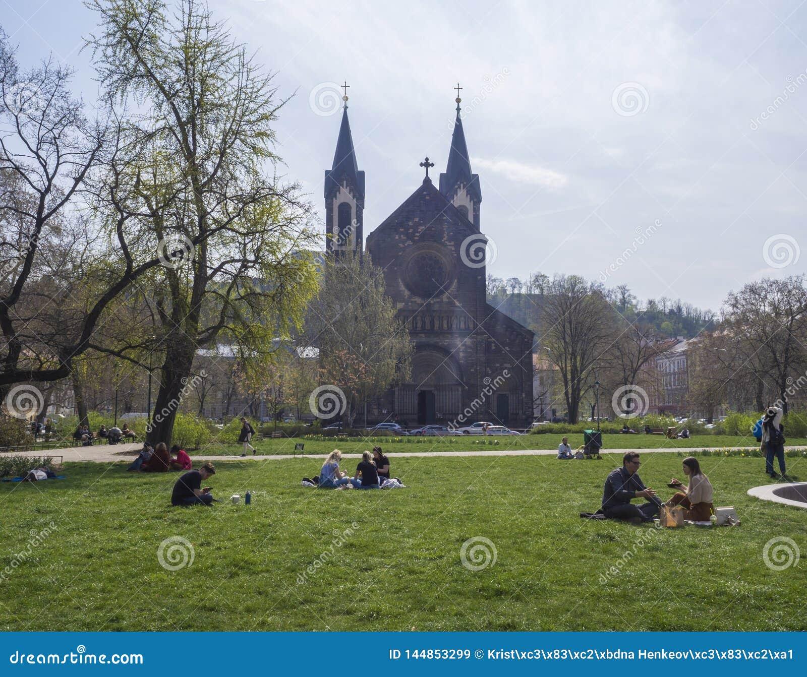 República Checa, Praga, el 13 de abril de 2019: grupo de personas que se relaja en hierba verde enorme y que disfruta de día de