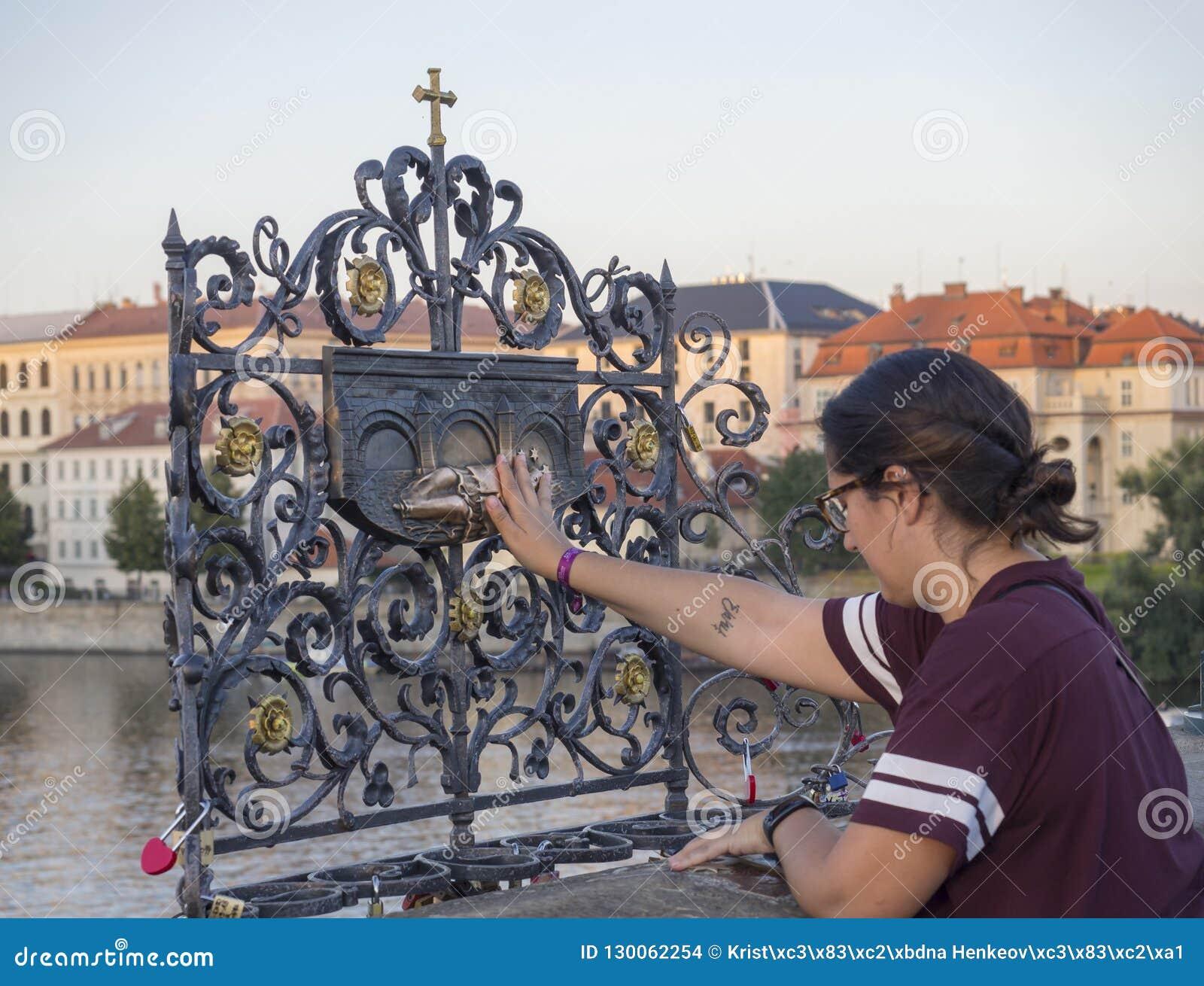 República Checa, Praga, el 8 de septiembre de 2018: Turista de la mujer joven que toca al sacerdote que cae Saint John de Nepomuk