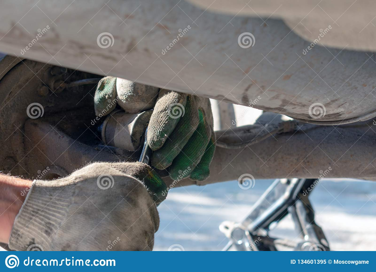 Repair of the car suspension. Gloved hand. Replacing the shock absorber strut
