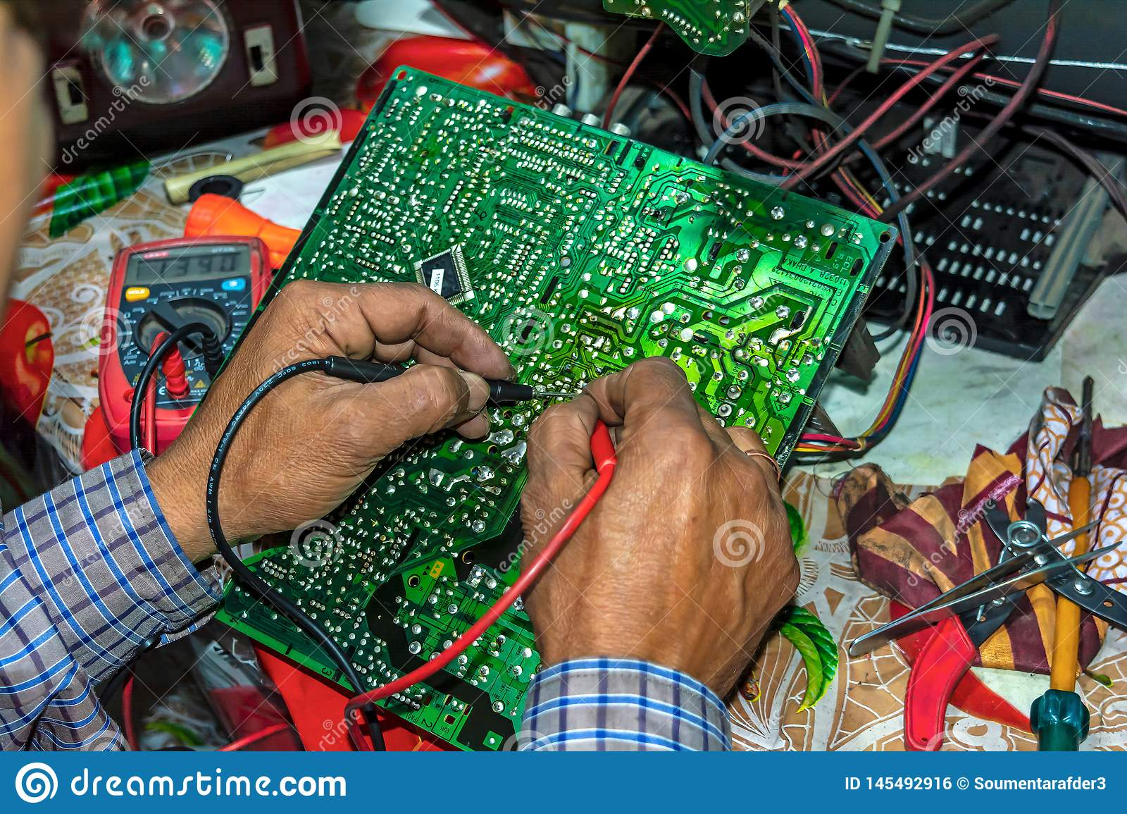 Repairing and checking of old TV motherboard with multimeter at home on the table