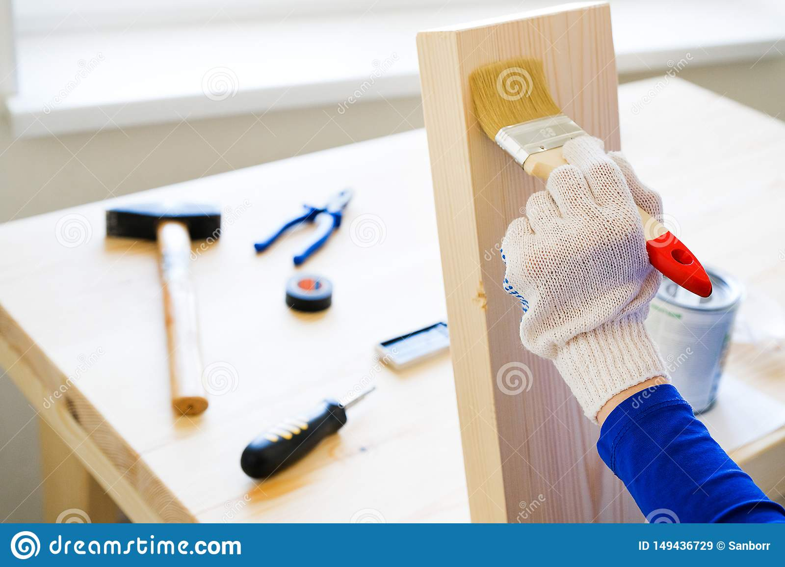 Repairman, carpenter, hired worker applies a protective varnish or paint brush on a wooden Board. Gloved hands, construction tools