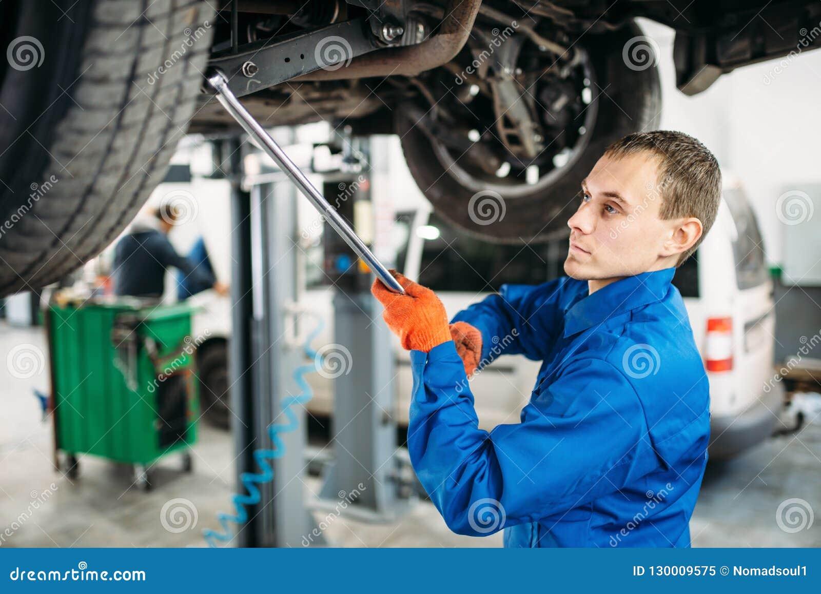 Repairman sprawdza zawieszenie, samochód na dźwignięciu
