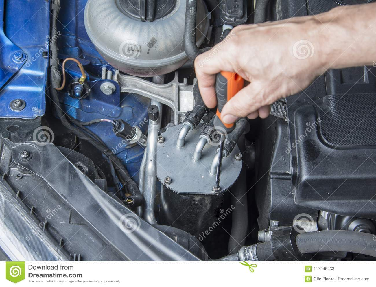 Repairman starts to change fuel filter in the car.