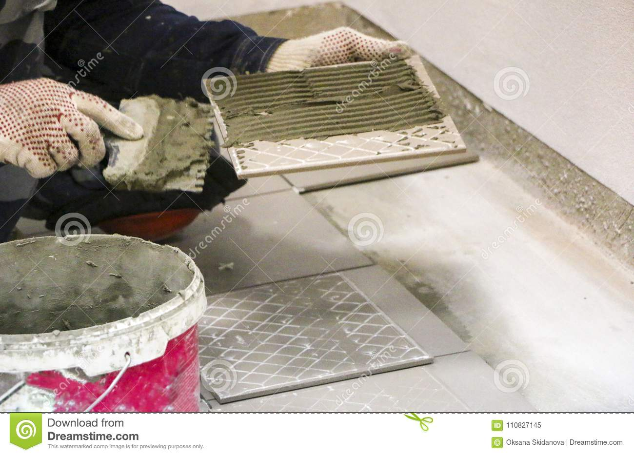 Repairs Laying Of Floor Ceramic Tiles Mens Hands In Gloves With