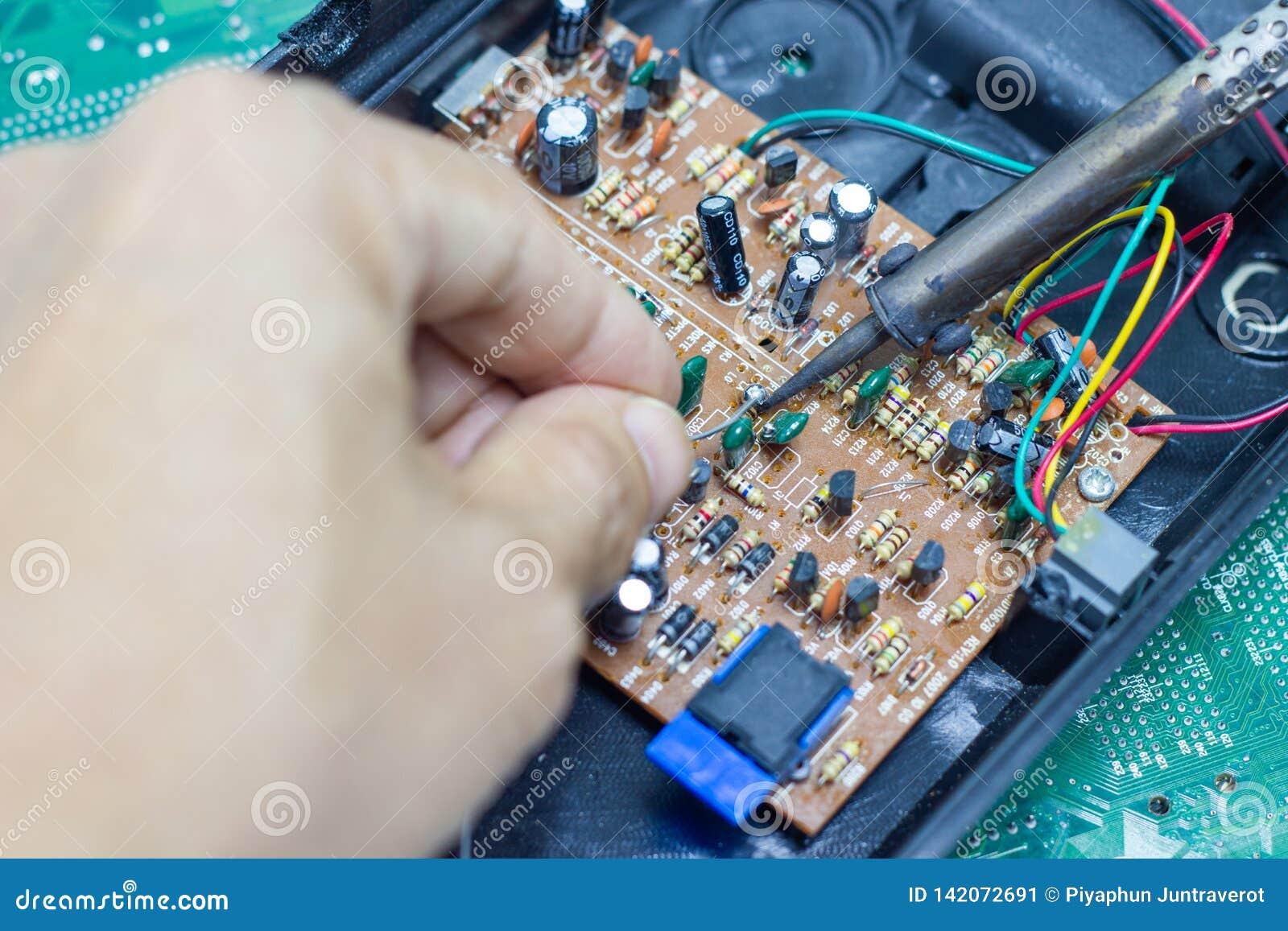 Reparação do técnico eletrônica da placa de circuito do computador por ferros de solda