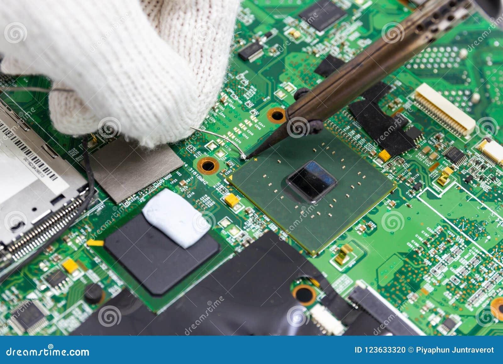 Reparação do técnico eletrônica da placa de circuito do ` s do computador por ferros de solda