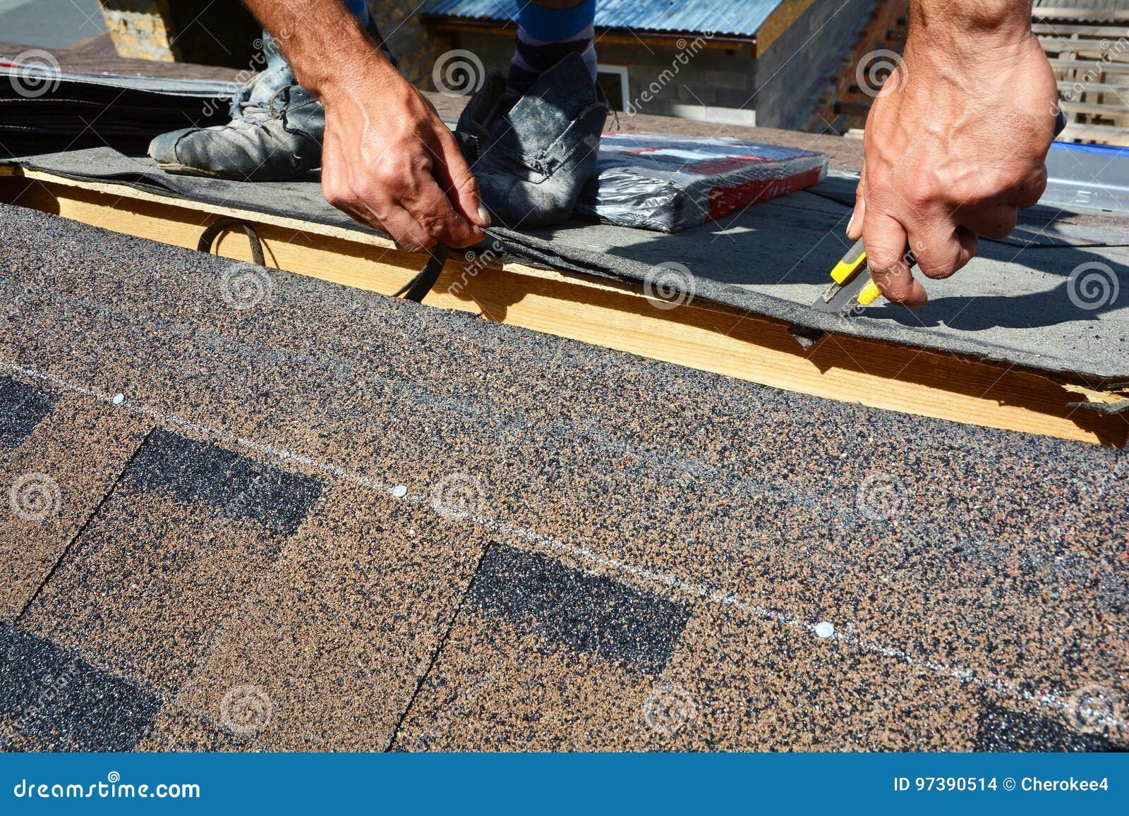 Reparación de una techumbre de tablas El fieltro o el betún de la techumbre del corte del Roofer durante la impermeabilización tr