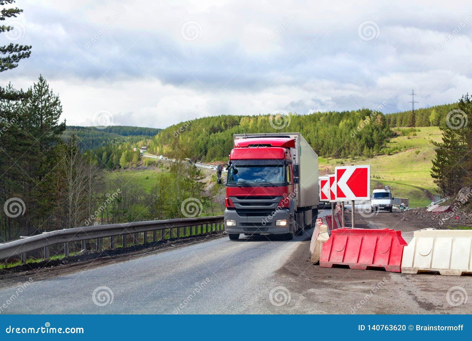Reparación del camino, muestra roja, tráfico en una manera, bosque verde y fondo del cielo nublado