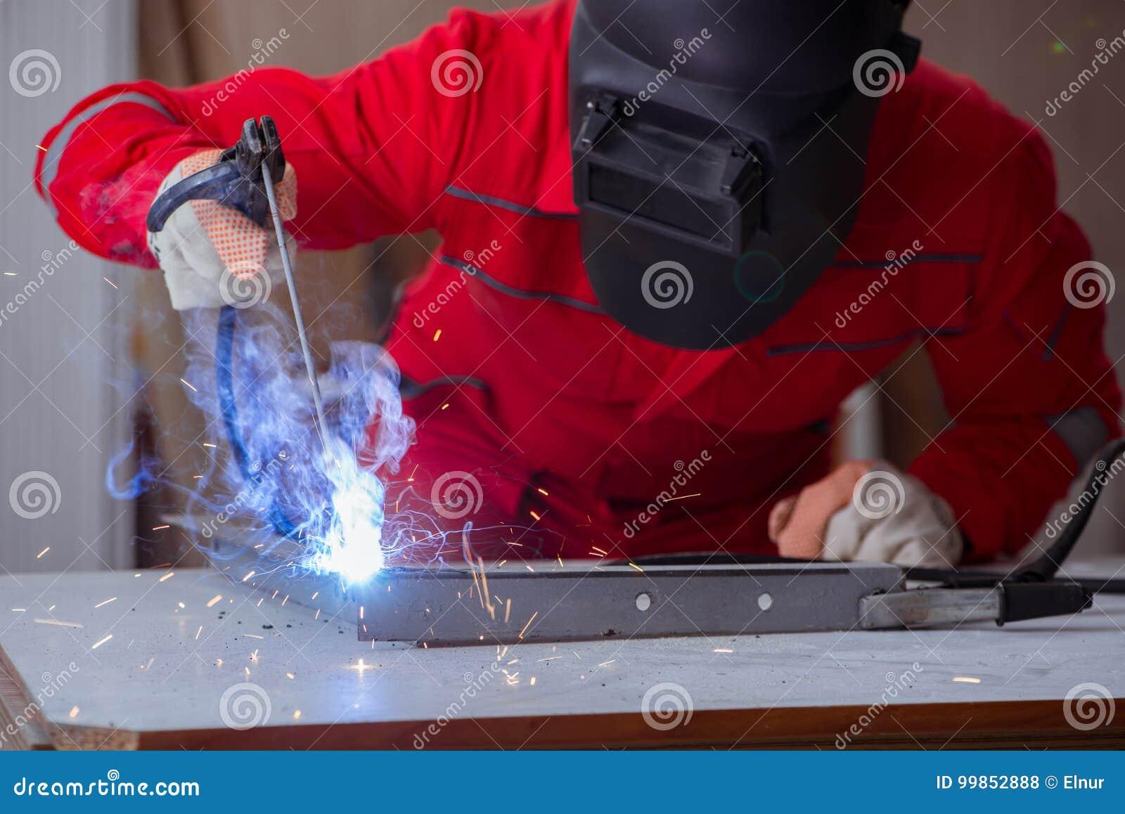reparador joven con un electrodo del arma de la soldadura y un