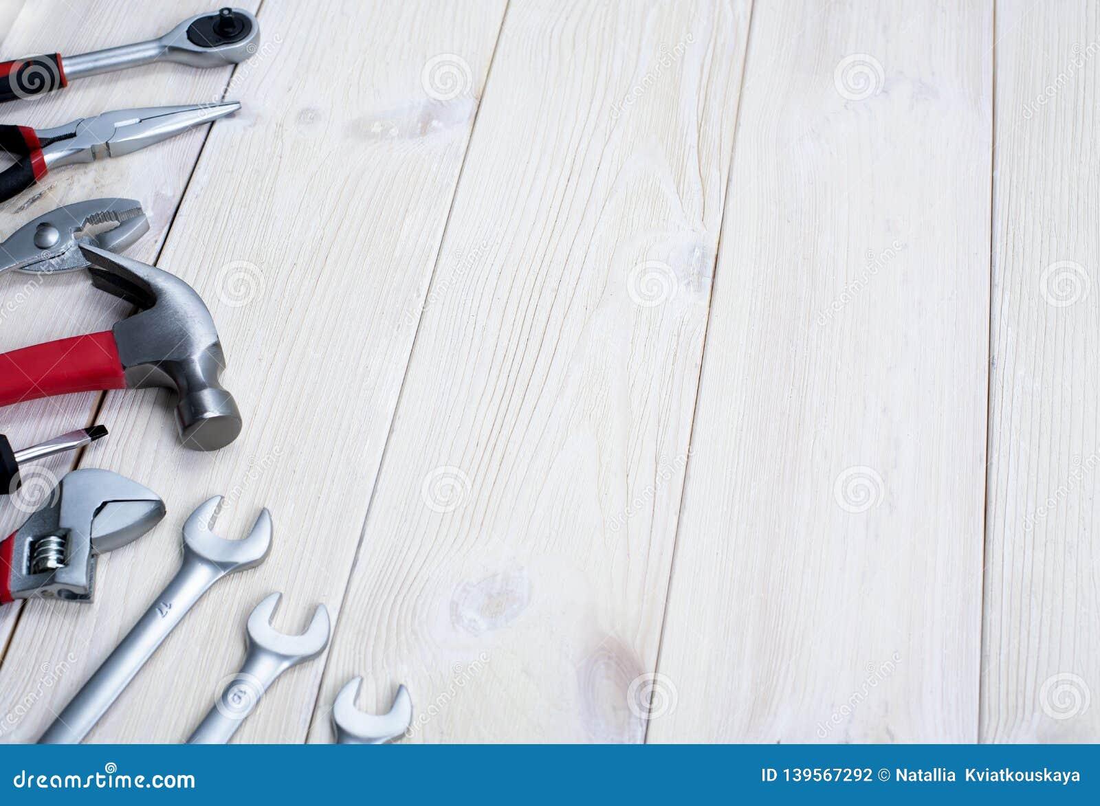 Reparatiehulpmiddelen op een witte houten achtergrond Jack sleutels en hamer Ruimte voor tekst