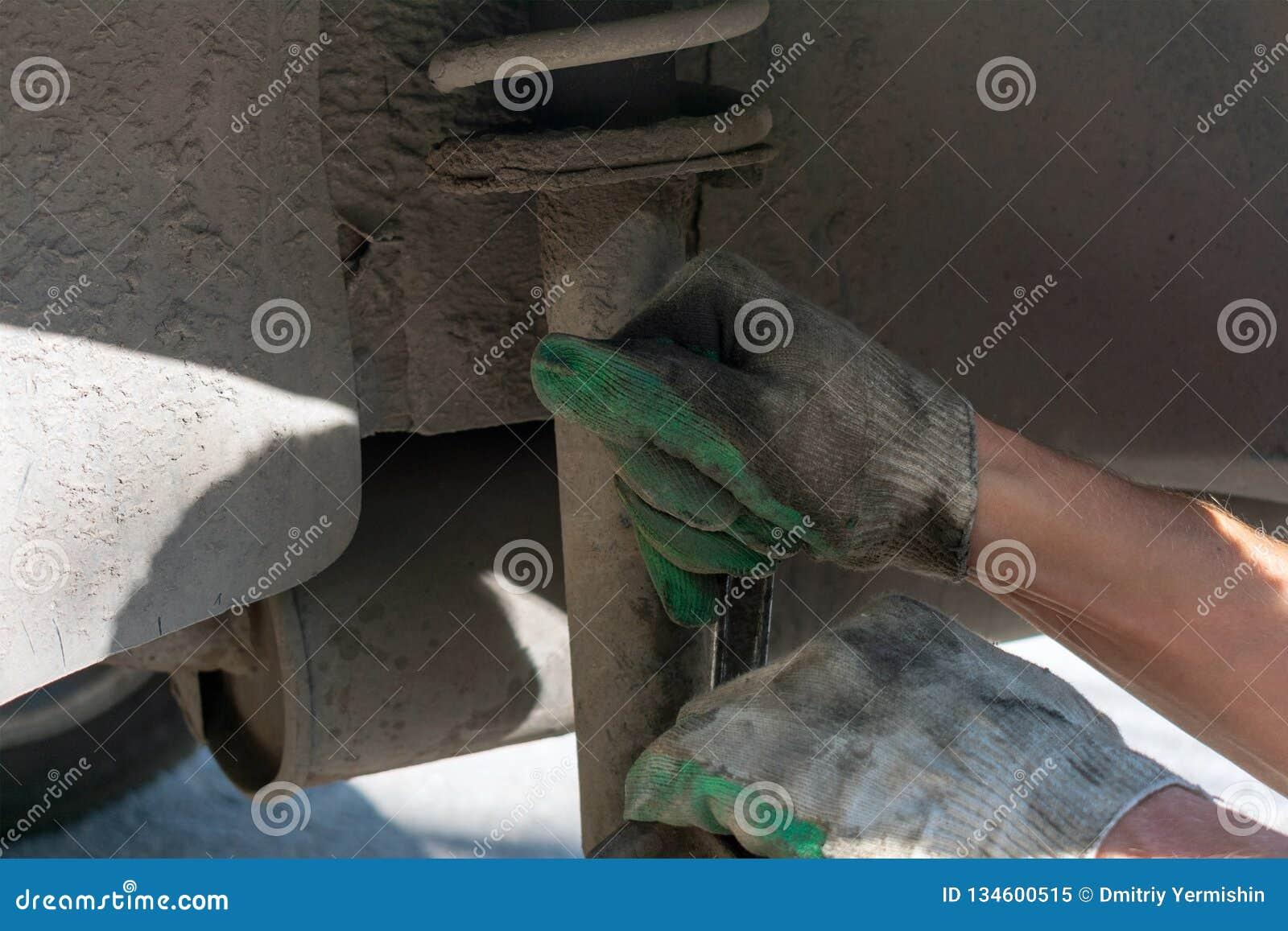 Reparatur der Autosuspendierung Behandschuhte Hand Ersetzen der Stoßdämpferspreize
