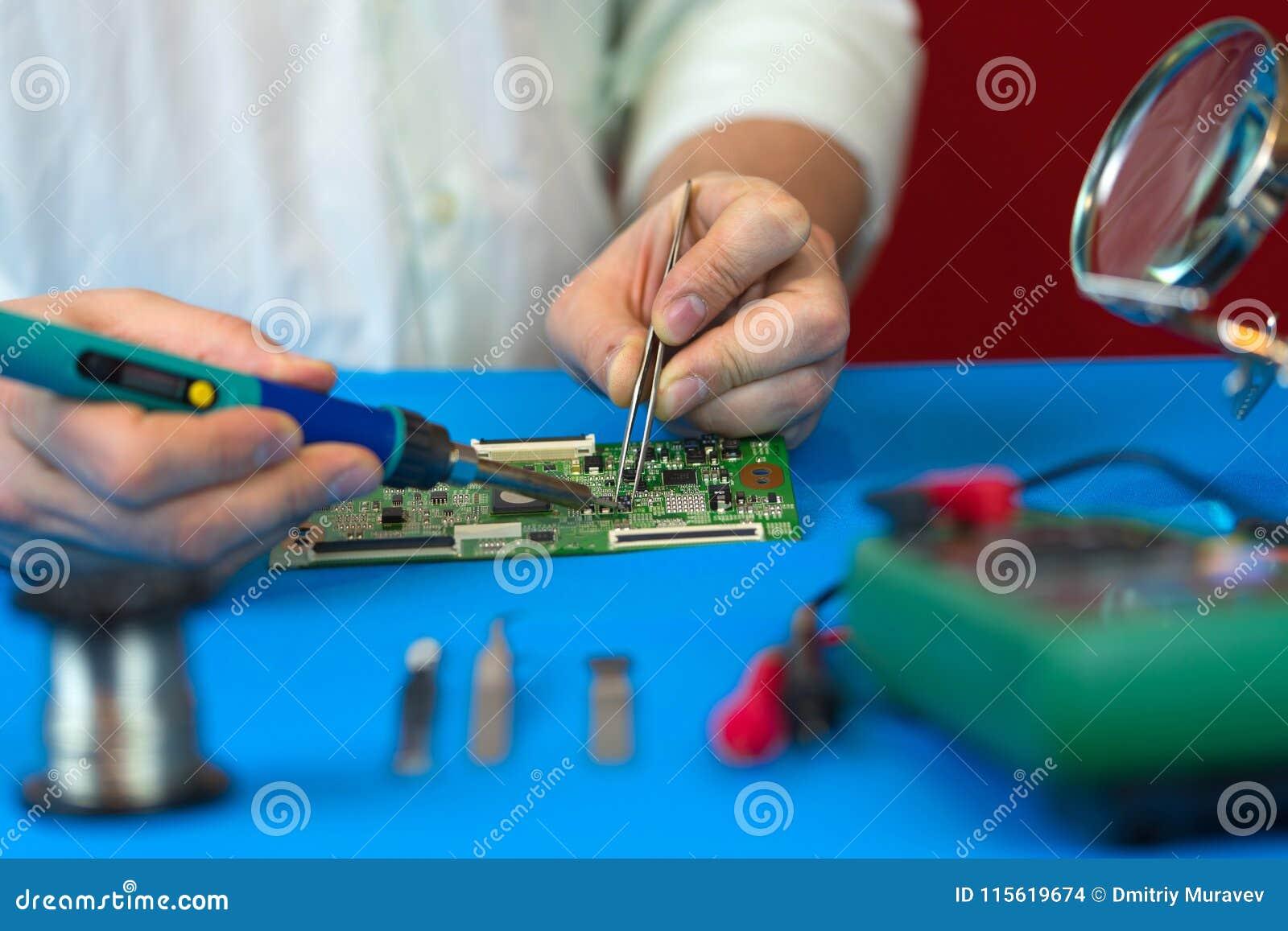 Reparatur des Videokonverterbrettes des Fernsehsignals Löten von elektronischen Bauelementen durch einen Ingenieur von modernen F