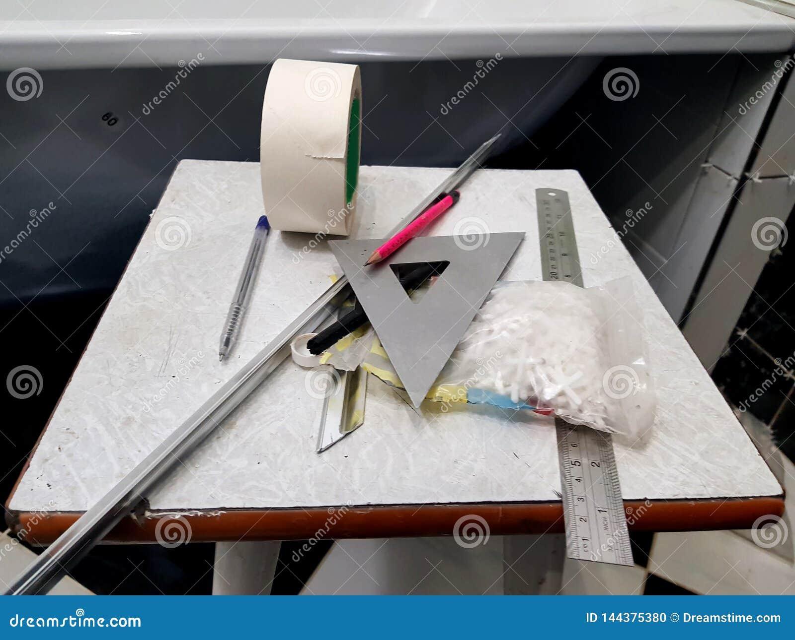 Reparatur - Geb?ude mit Werkzeugen, Ma?band, Bleistift, Stift, Markierung, selbsthaftendes Kreppband, Dreieck, Ecke, Fliesenecken