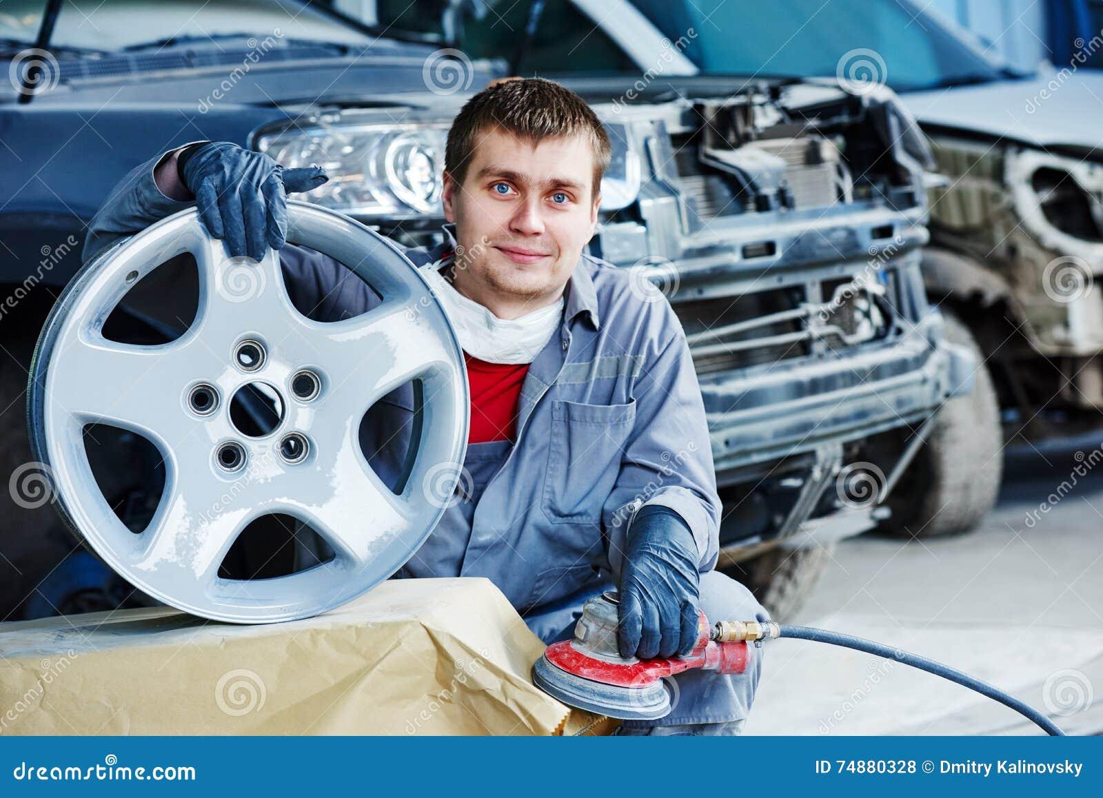 Repare o trabalhador do mecânico com a borda do disco da roda de carro da liga clara
