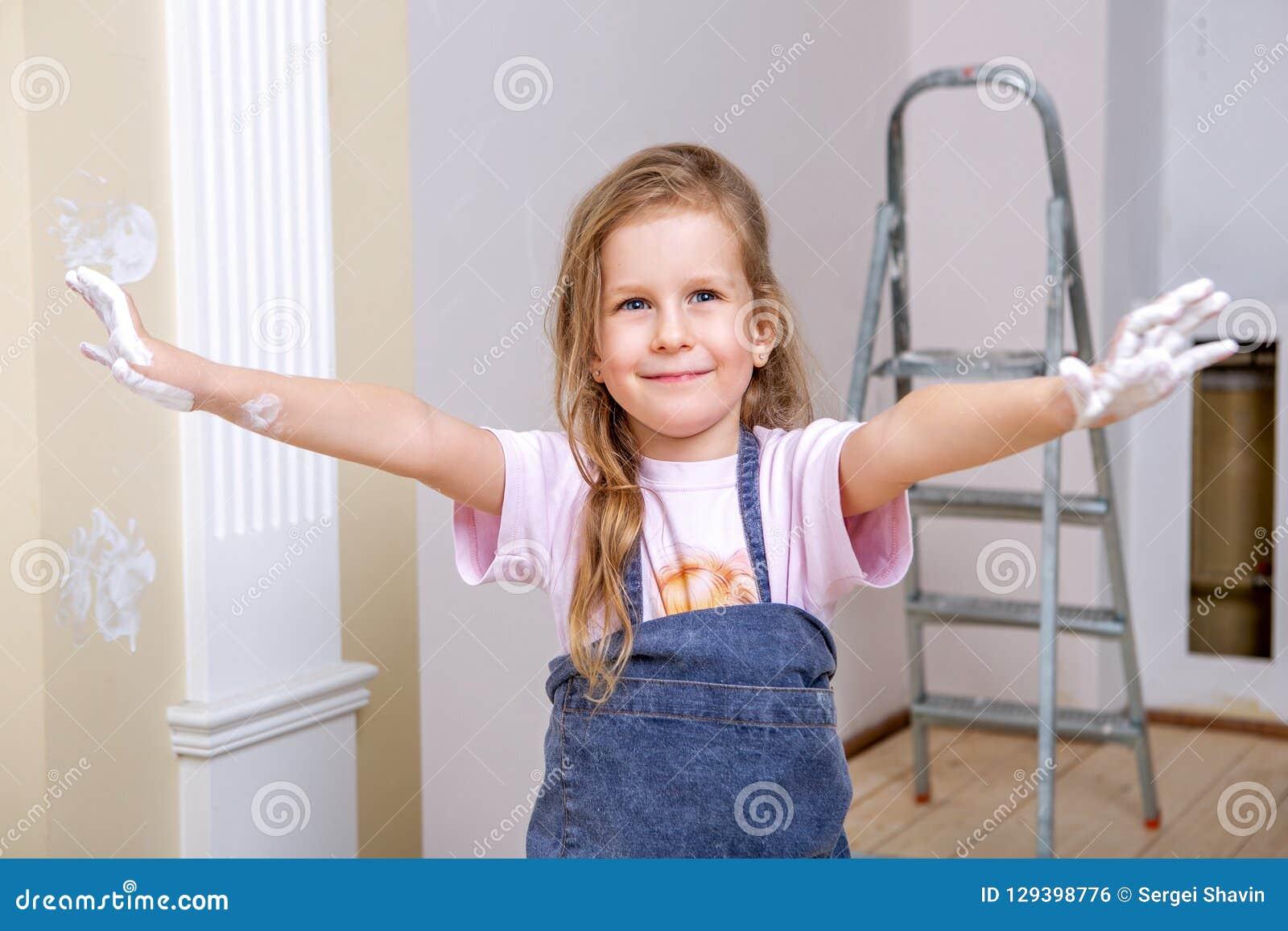 Reparo no apartamento A mãe e a filha felizes da família nos aventais pintam a parede com pintura branca A menina mostra-lhe as p