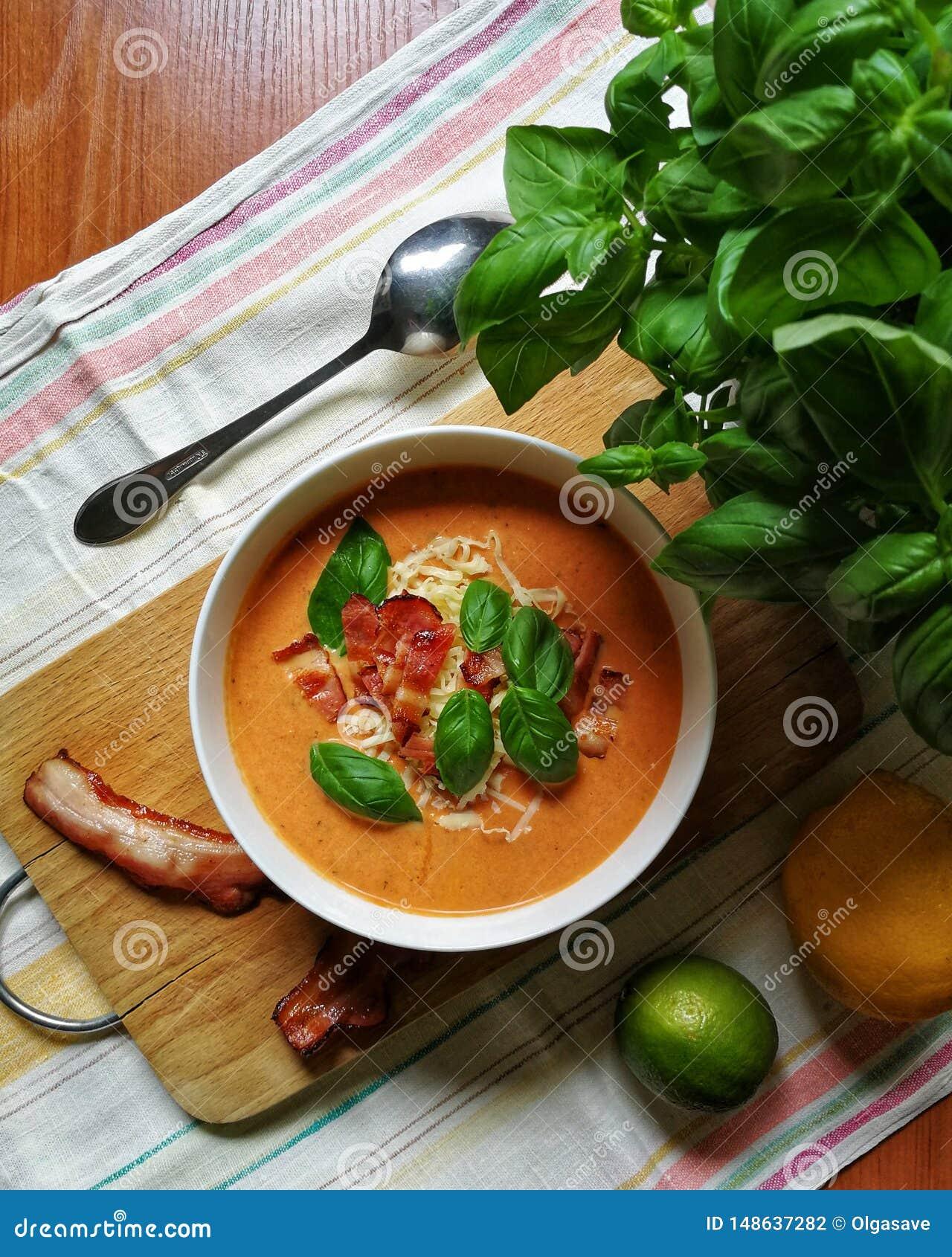 Repas d?licieux Soupe crème à Tomatoe avec le basilic, le fromage, le lard et la chaux