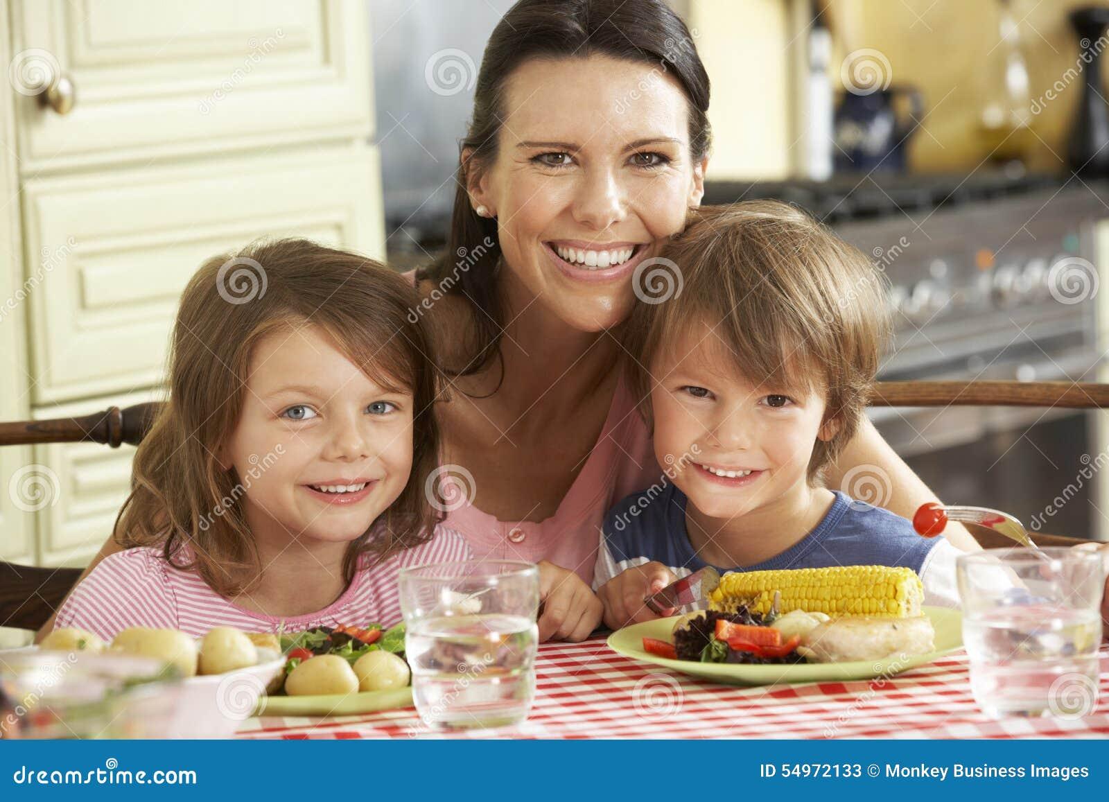 Repas de portion de mère aux enfants dans la cuisine
