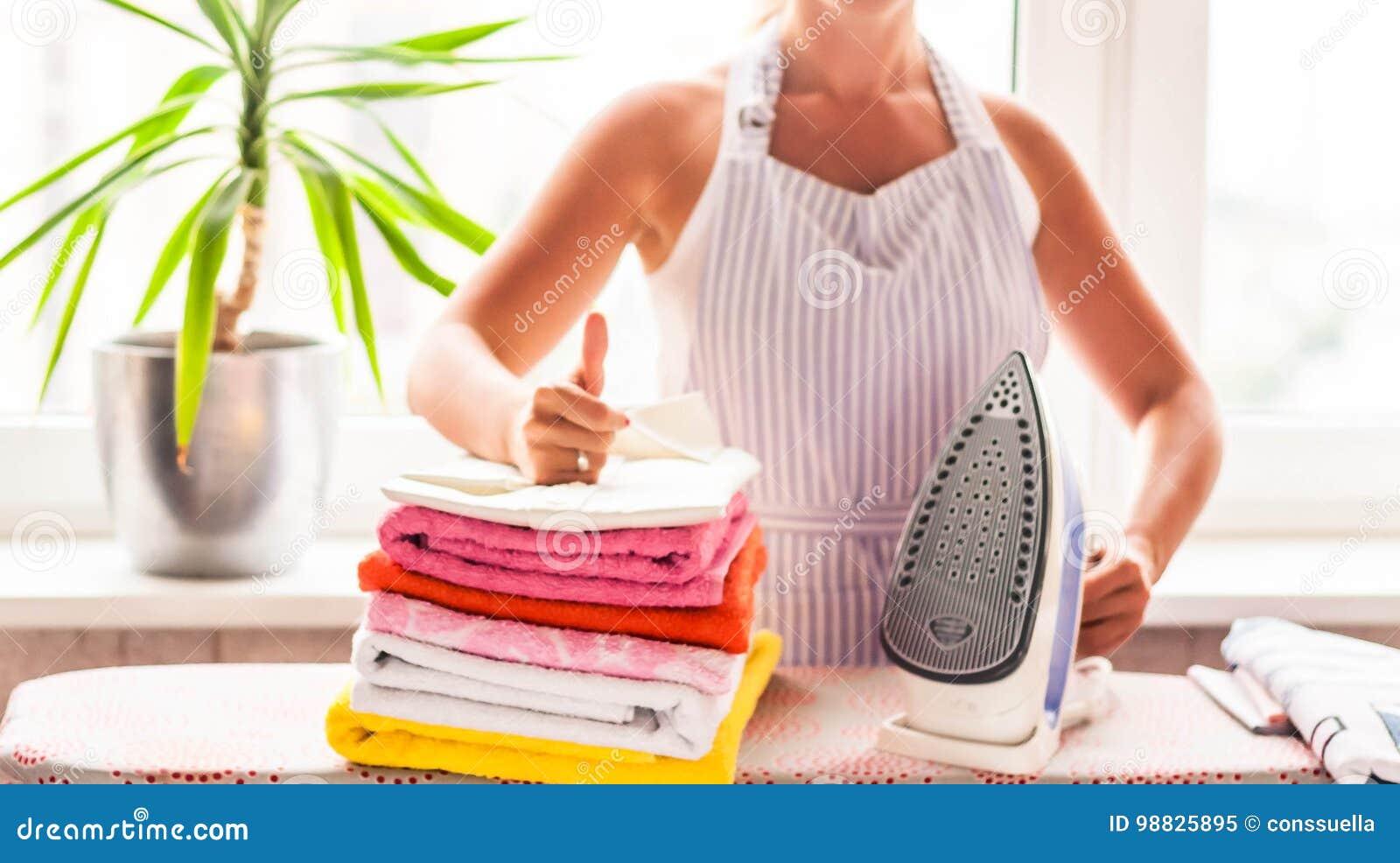 Repassant vêtx sur la planche à repasser, les vêtements repassés repassant, la blanchisserie, vêtements, ménage et objecte le con