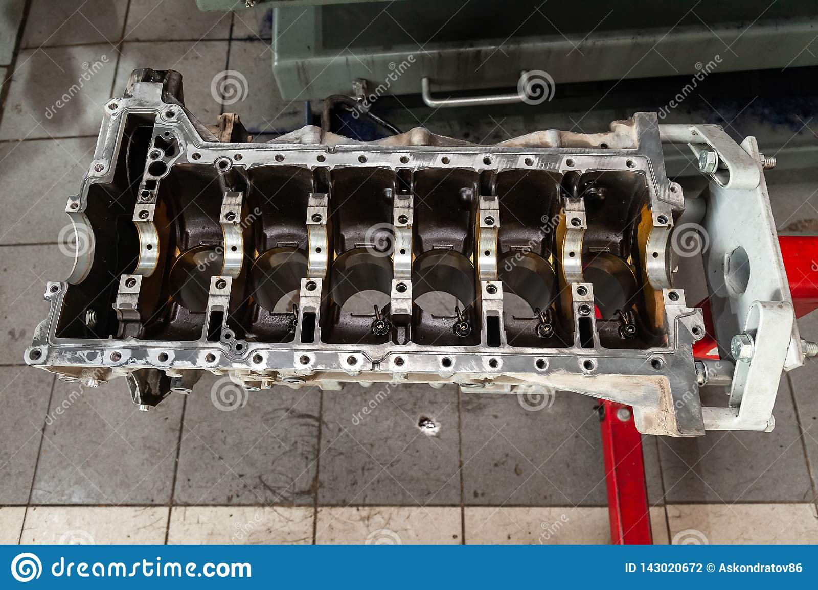 Replacement engine used on a crane mounted for installation on a car after a breakdown and repair in a car repair workshop as a