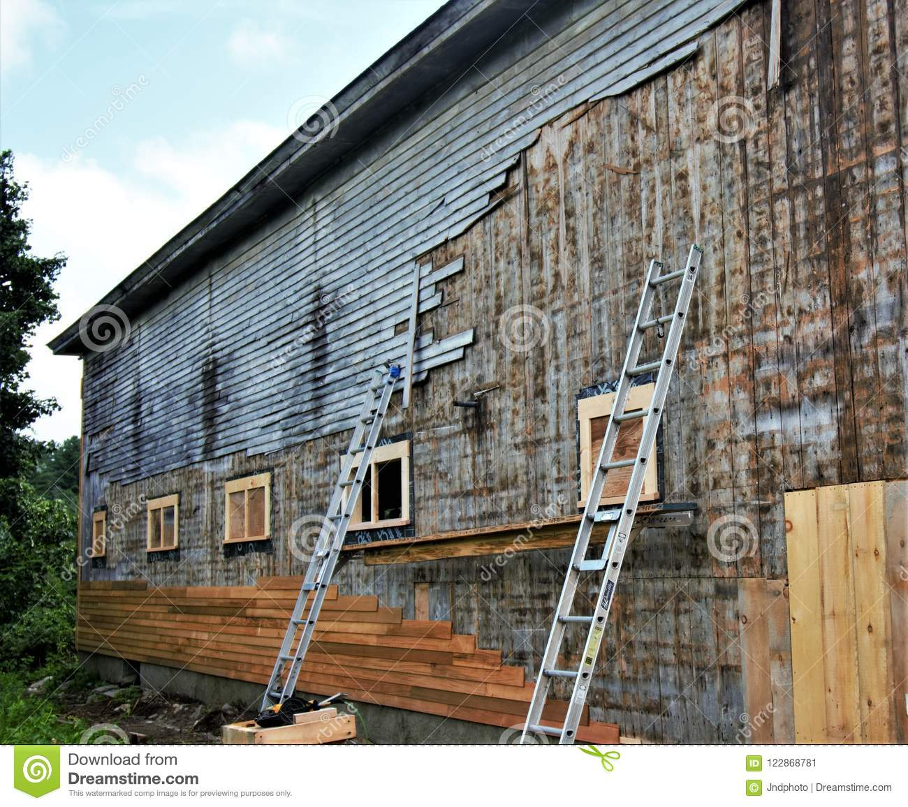 Replacing The Old Gray Siding Of Old Wooden Barn With New