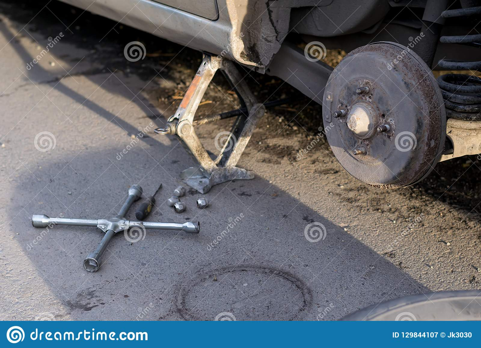 Replacing the rear wheel of the car. The car is mounted on the Jack. On the road lie screws, tool and wheel.