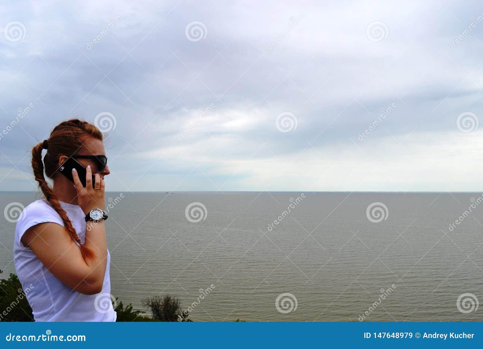 Repos Portrait extérieur d une belle femme heureuse de brune dans les lunettes de soleil et le chapeau parlant à son téléphone po