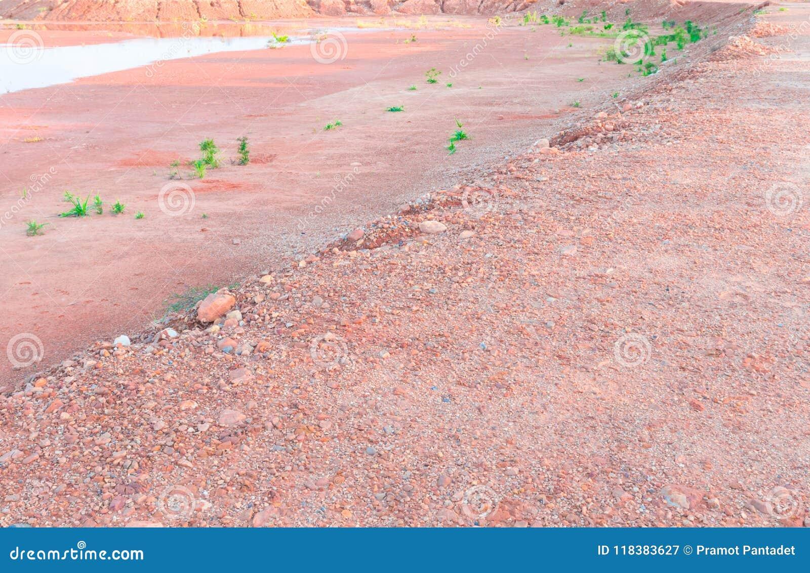 Represe a água seca do verão e afie a terra alaranjada do solo alaranjado de pedra do assoalho das texturas no fundo da natureza