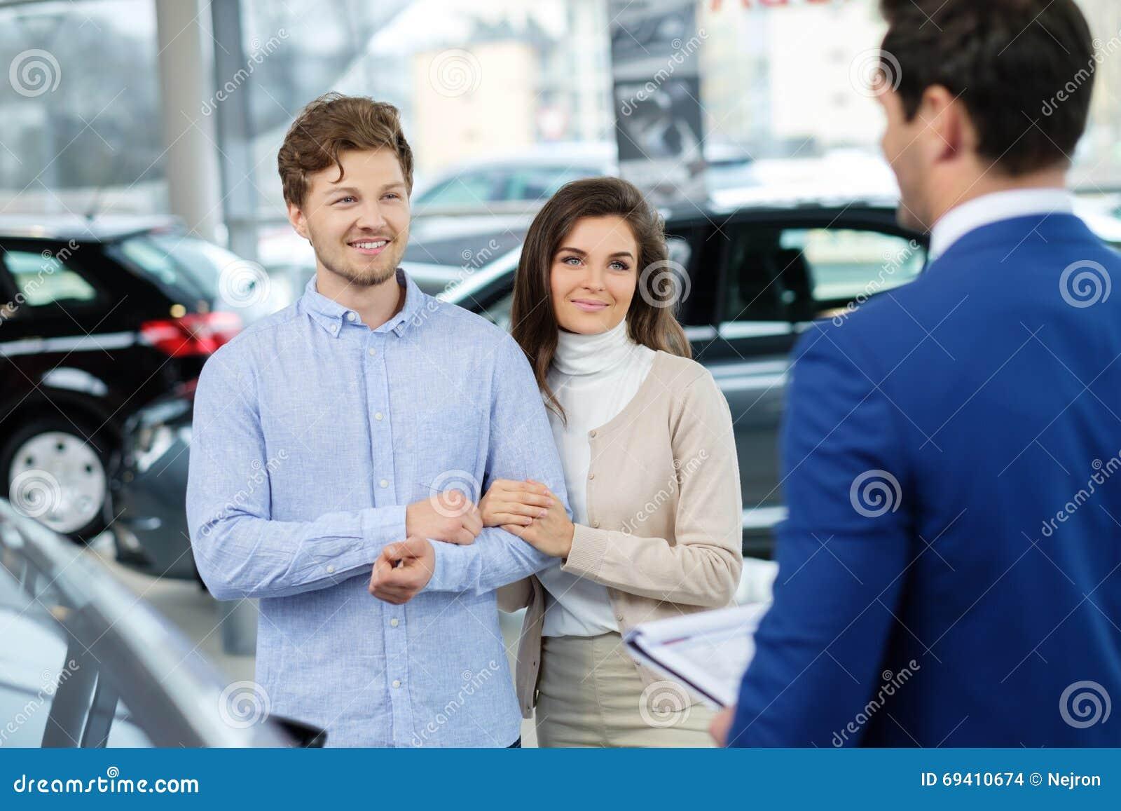 Representant som talar till ett ungt par på återförsäljarevisningslokalen