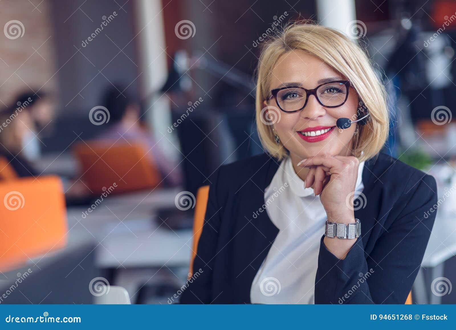 Representante de serviço ao cliente no trabalho Jovem mulher bonita nos auriculares que trabalham no computador