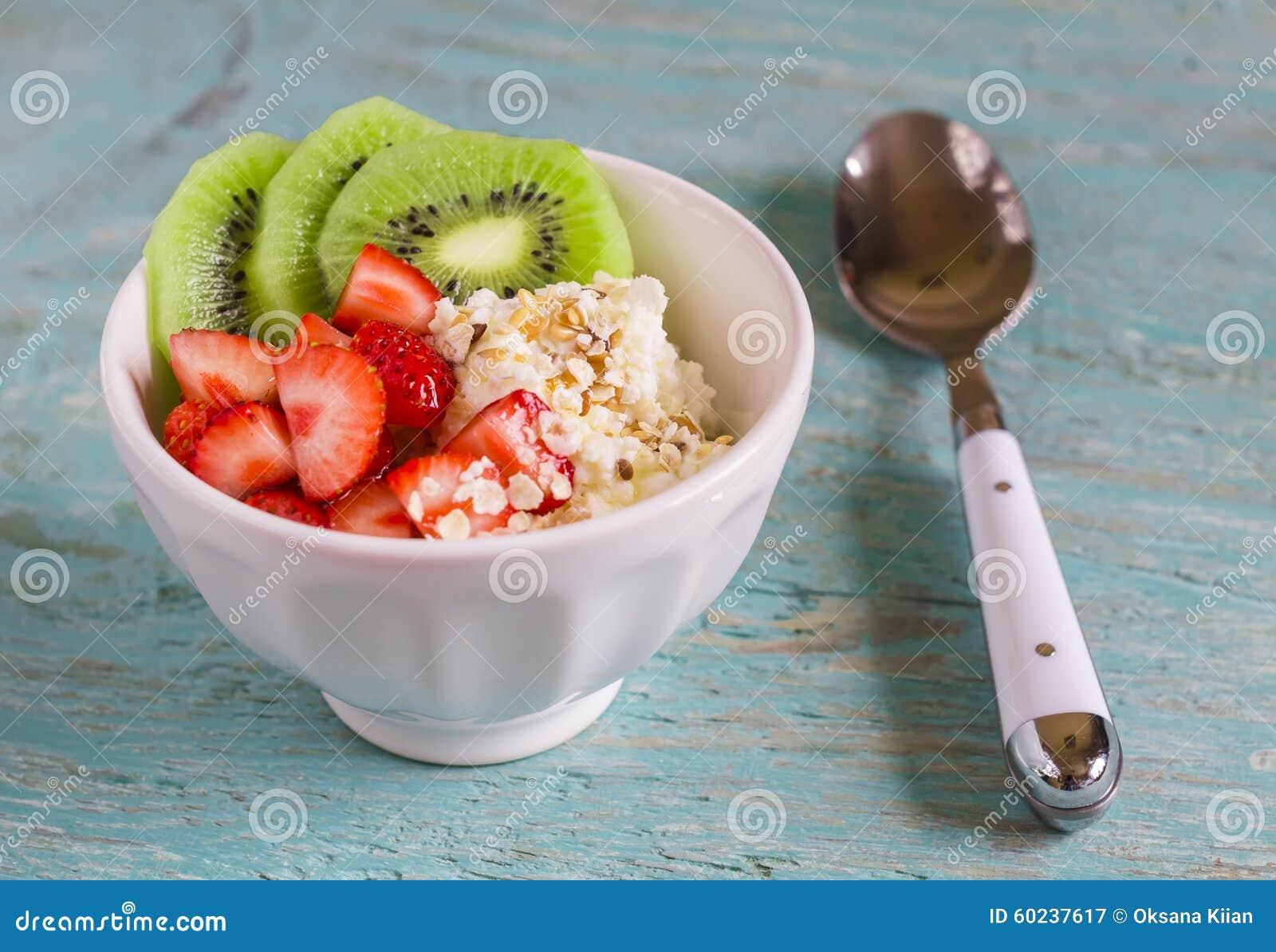 Requeijão com morangos, quivi, mel, cereais e sementes do linho - um alimento saudável, café da manhã saboroso e saudável ou peti