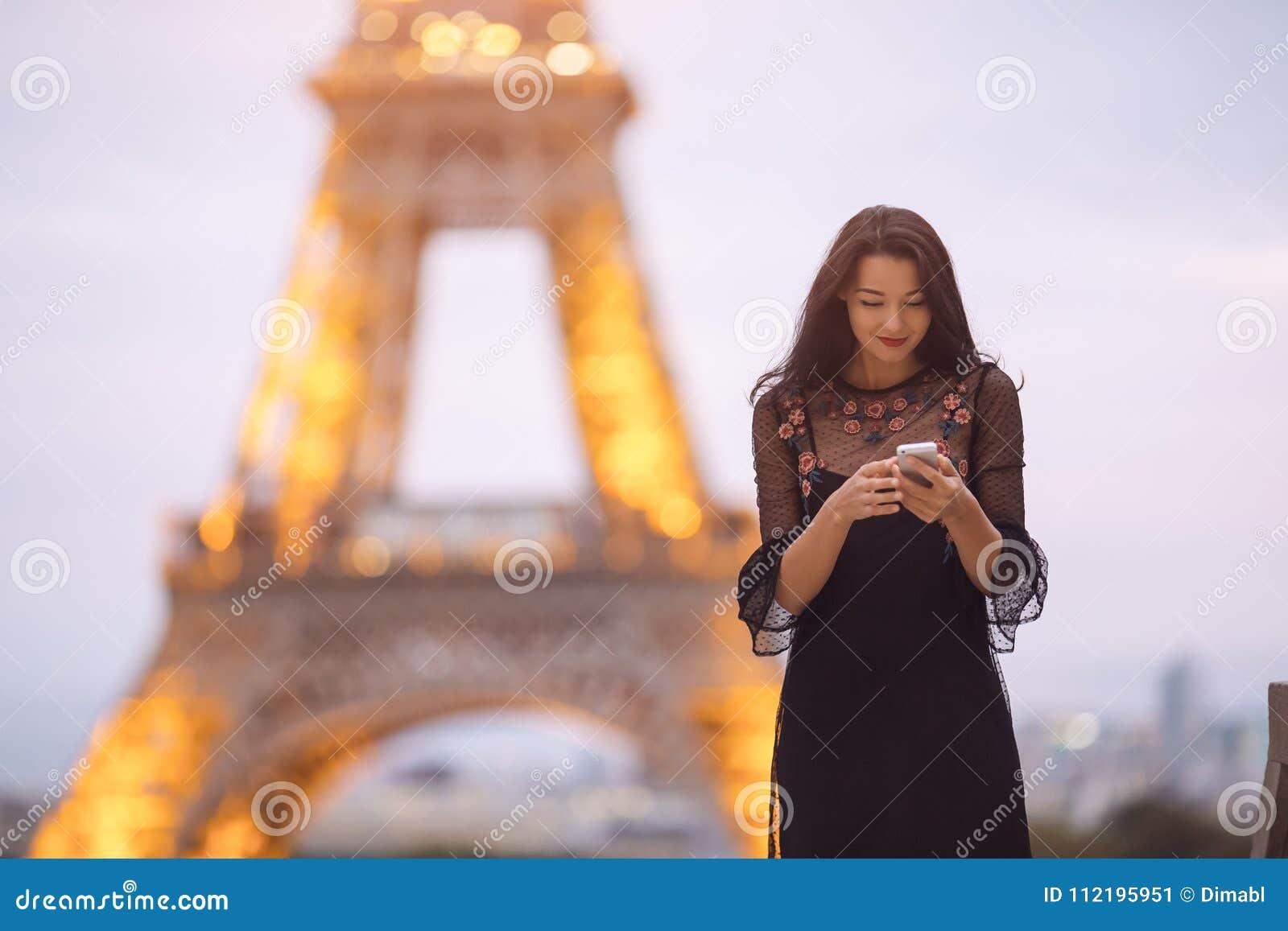 Resa kvinnan som använder smartphonen nära Eiffeltorn och karusellen, Paris Bullrig bild för afton lite