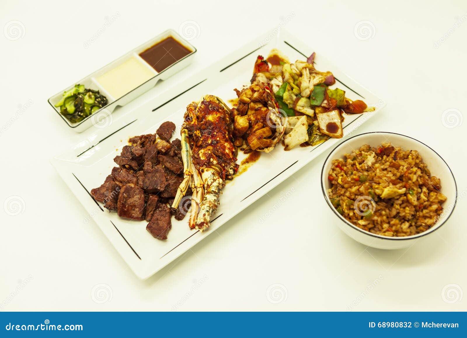 Resaca y césped, langosta frita y participación jugosa con un adorno de verduras fritas con con arroz y salsas calientes chinos f