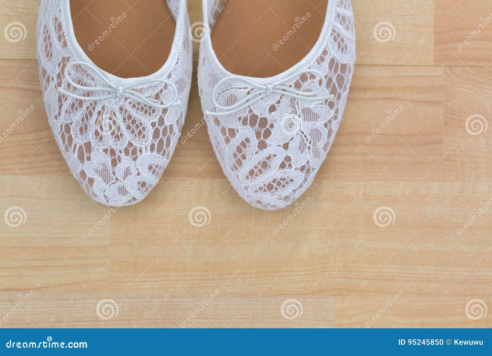 Resbalón plano del ballet floral blanco del cordón en los zapatos en fondo de madera