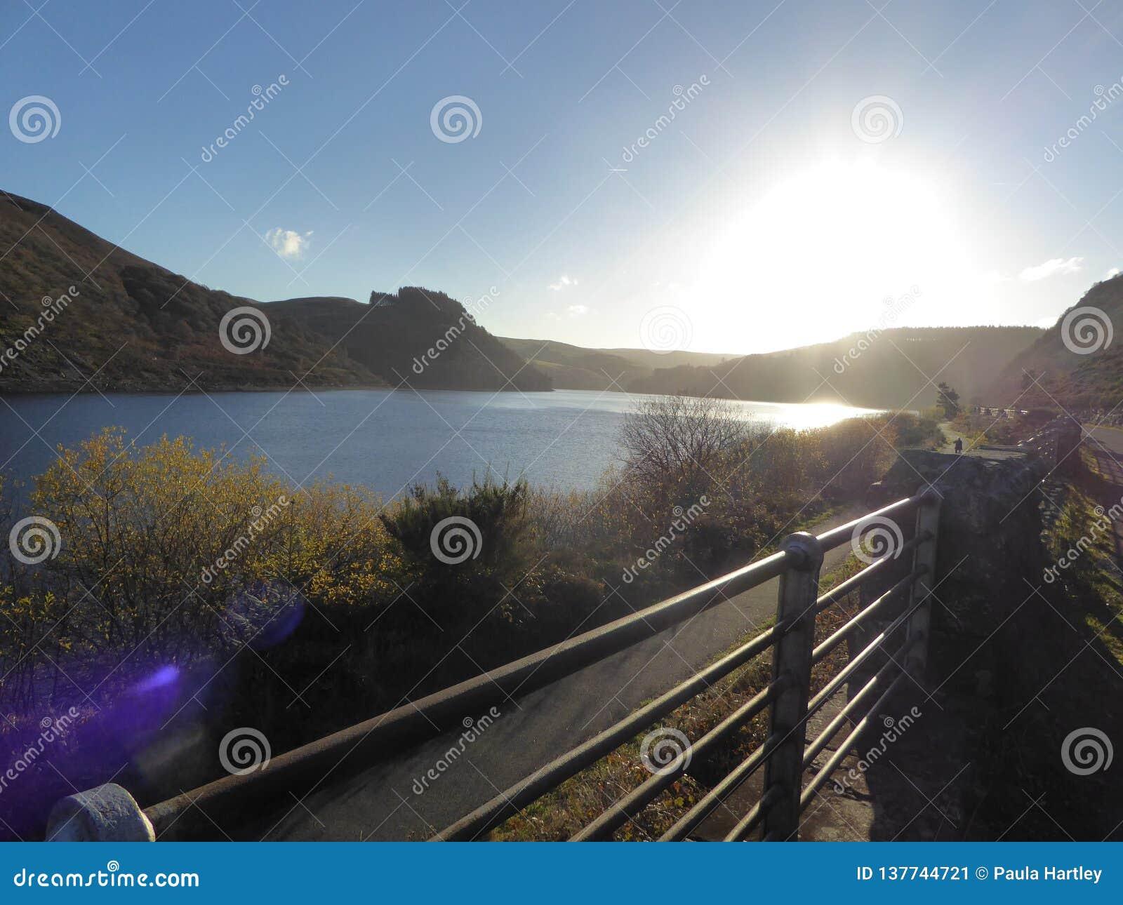 Reservatórios de Elan Valley, Gales com o sol que vai para baixo em céus azuis