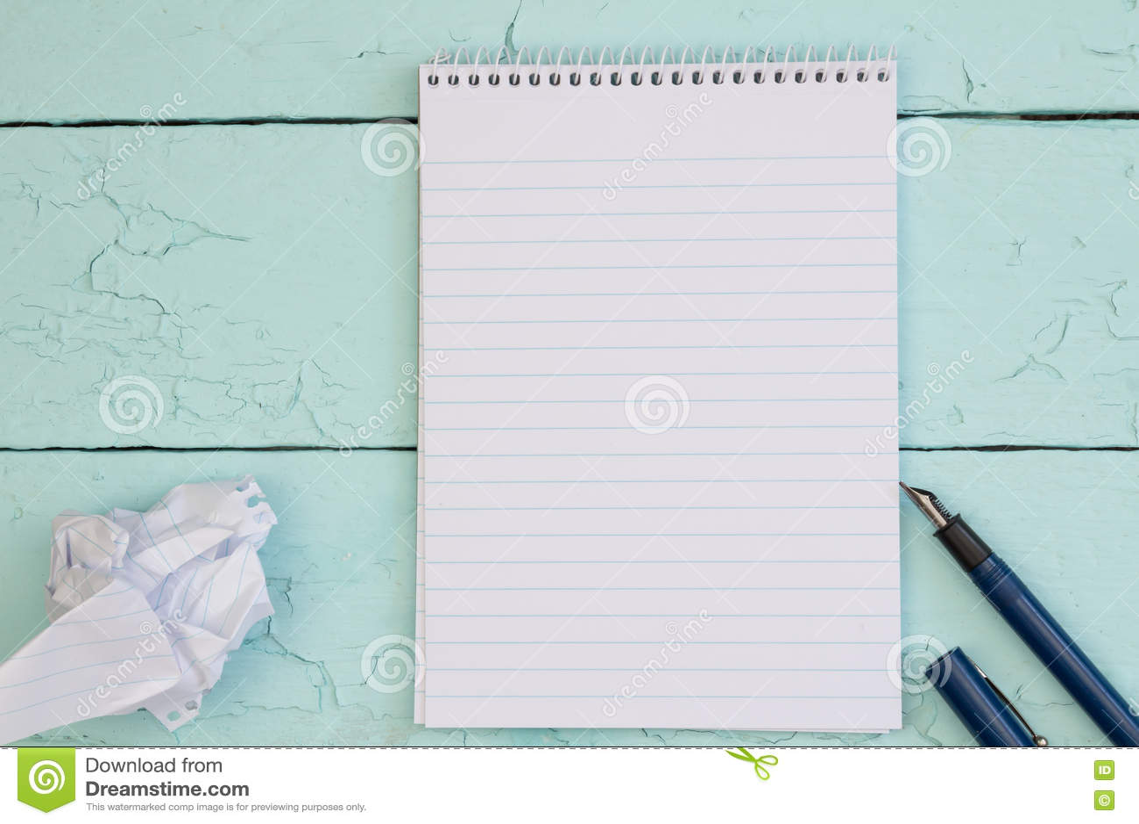 Reservoarpenna och tomt papper på den lantliga wood tabellen för turkos