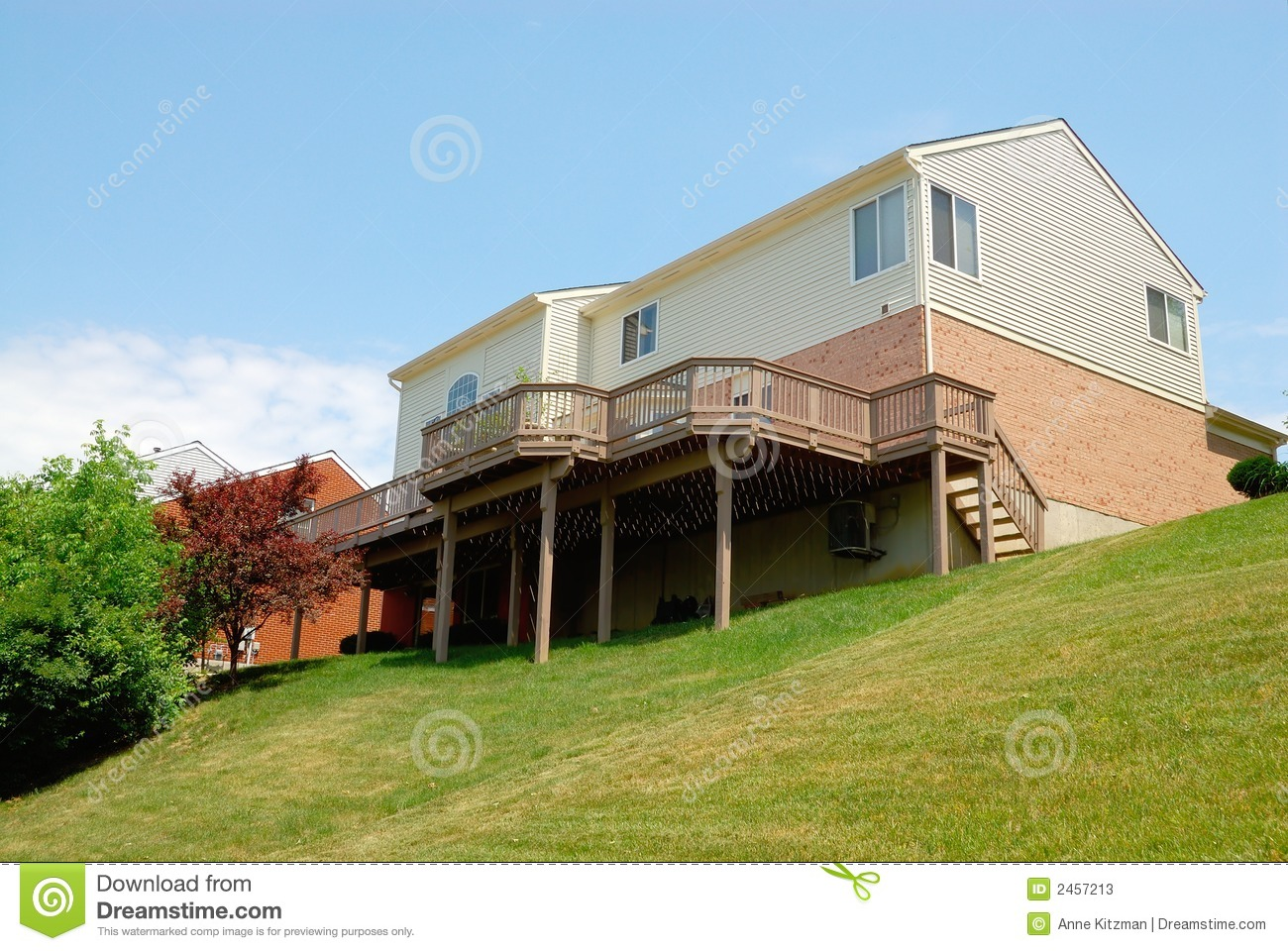 residential 2 story brick house sitting on a sloped back yard